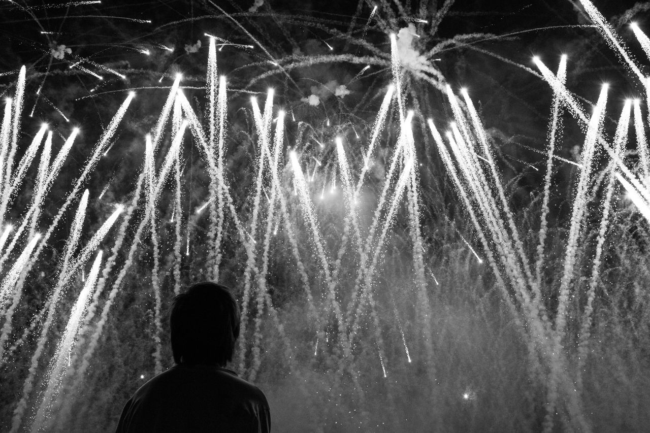 motion, celebration, night, long exposure, glowing, rear view, leisure activity, exploding, lifestyles, low angle view, firework display, arts culture and entertainment, blurred motion, event, firework - man made object, enjoyment, sparks, entertainment, outdoors, sky, vacations