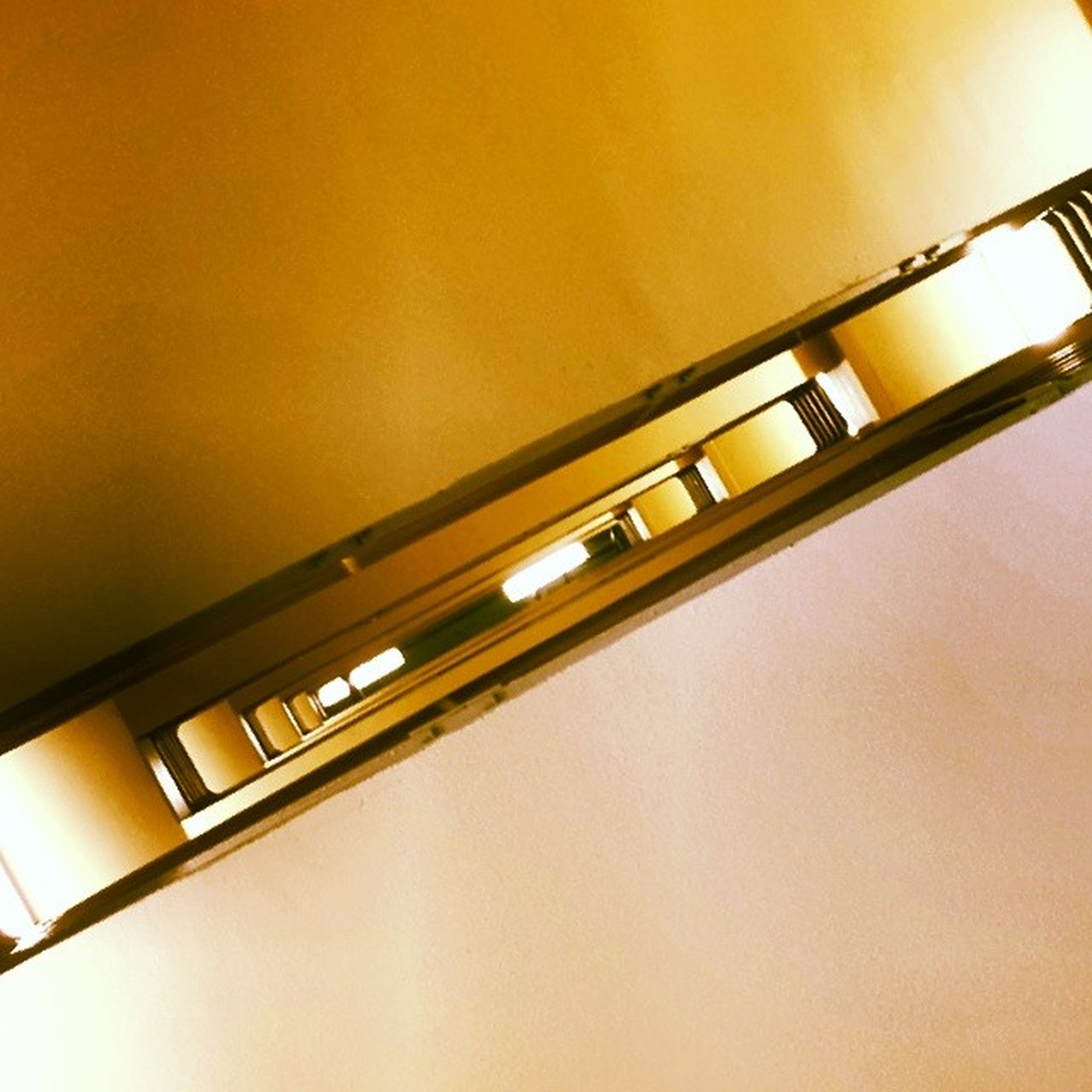 indoors, low angle view, copy space, wall - building feature, built structure, architecture, lighting equipment, yellow, no people, ceiling, wall, illuminated, metal, sunlight, home interior, orange color, railing, electricity, close-up, light - natural phenomenon