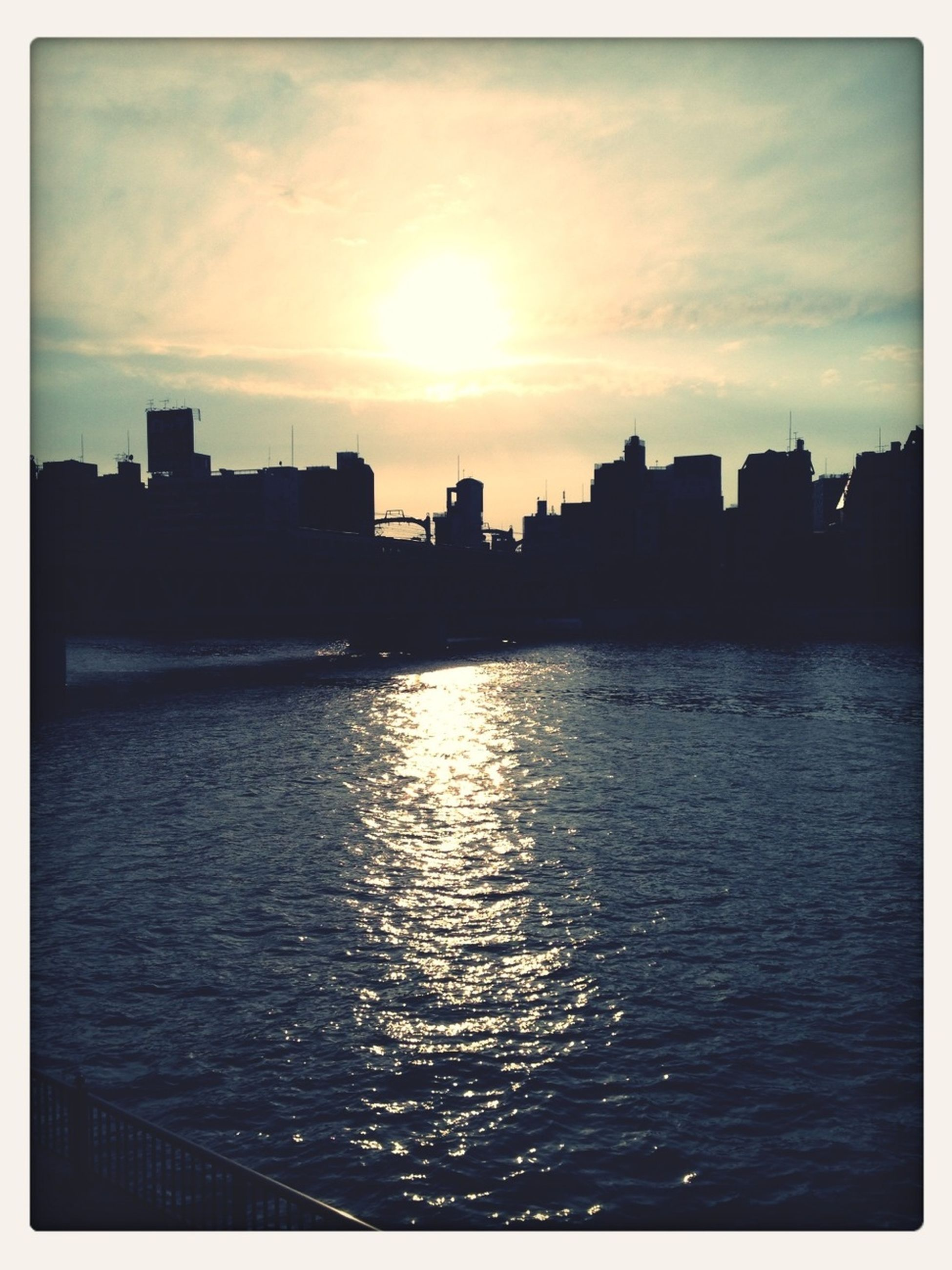sunset, silhouette, water, transfer print, waterfront, sky, sea, building exterior, architecture, built structure, auto post production filter, scenics, rippled, sun, beauty in nature, reflection, tranquil scene, tranquility, nature, cloud - sky