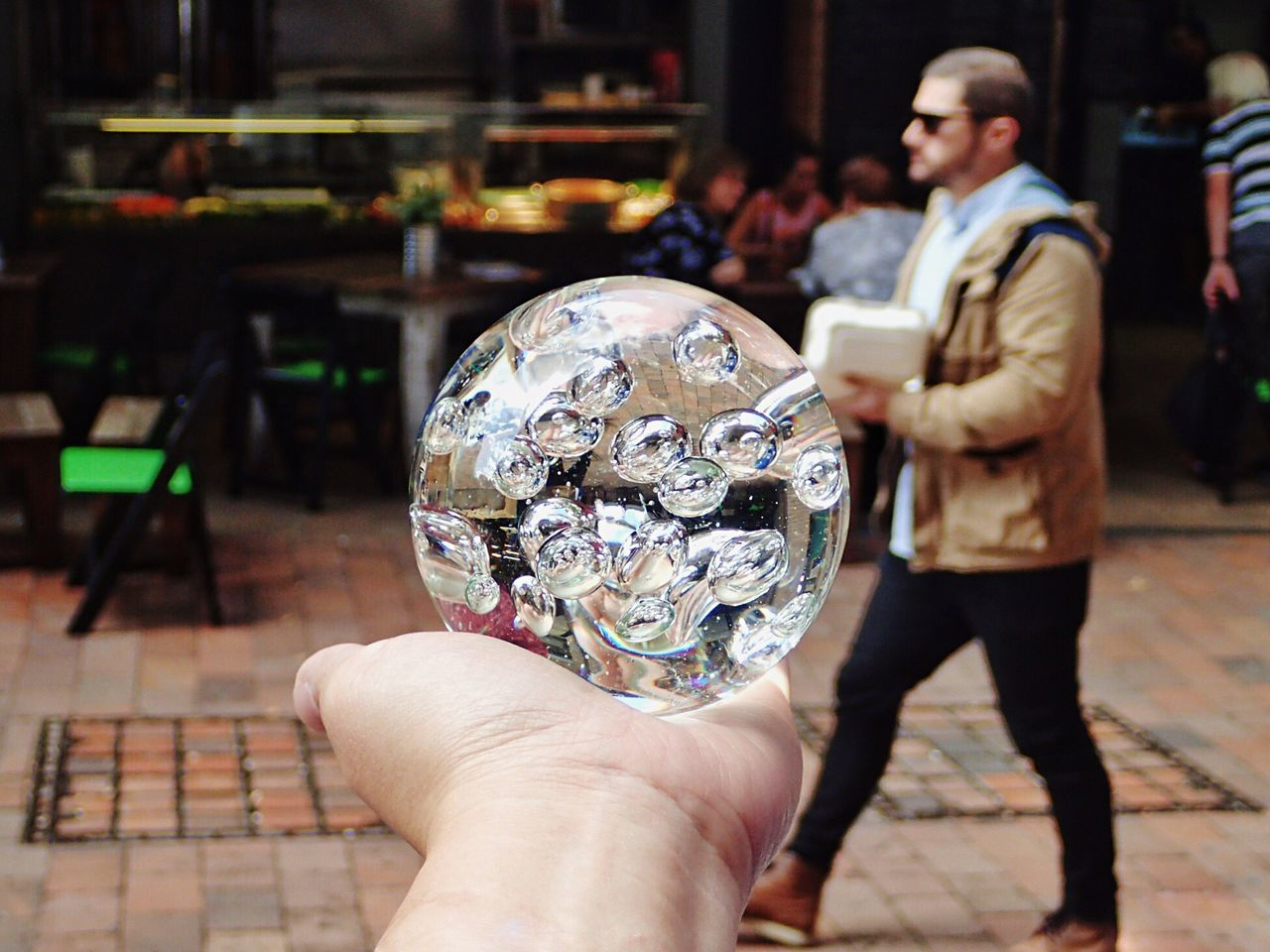 Close-Up Of Human Hand Holding Crystal Ball