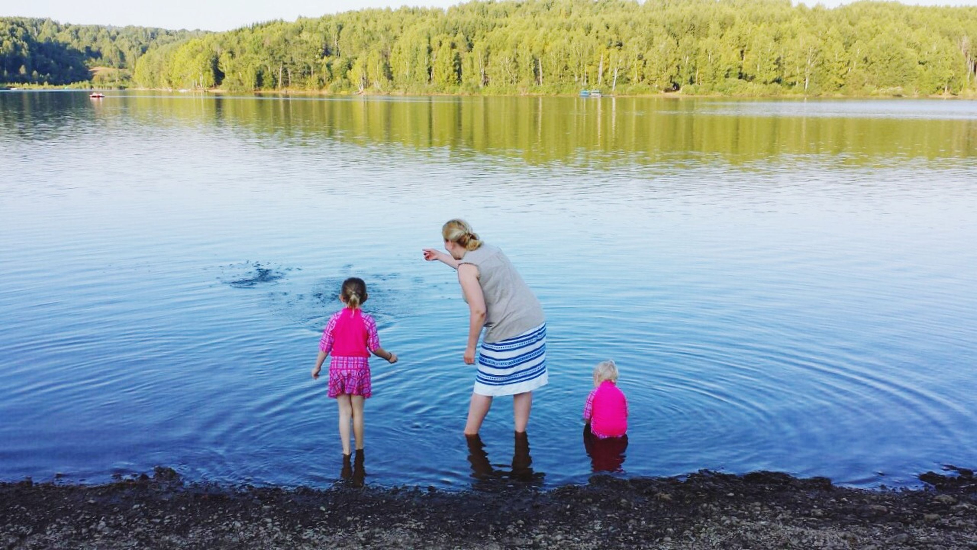 water, lake, lifestyles, leisure activity, full length, childhood, rear view, reflection, boys, togetherness, nature, standing, casual clothing, tranquility, girls, elementary age, day