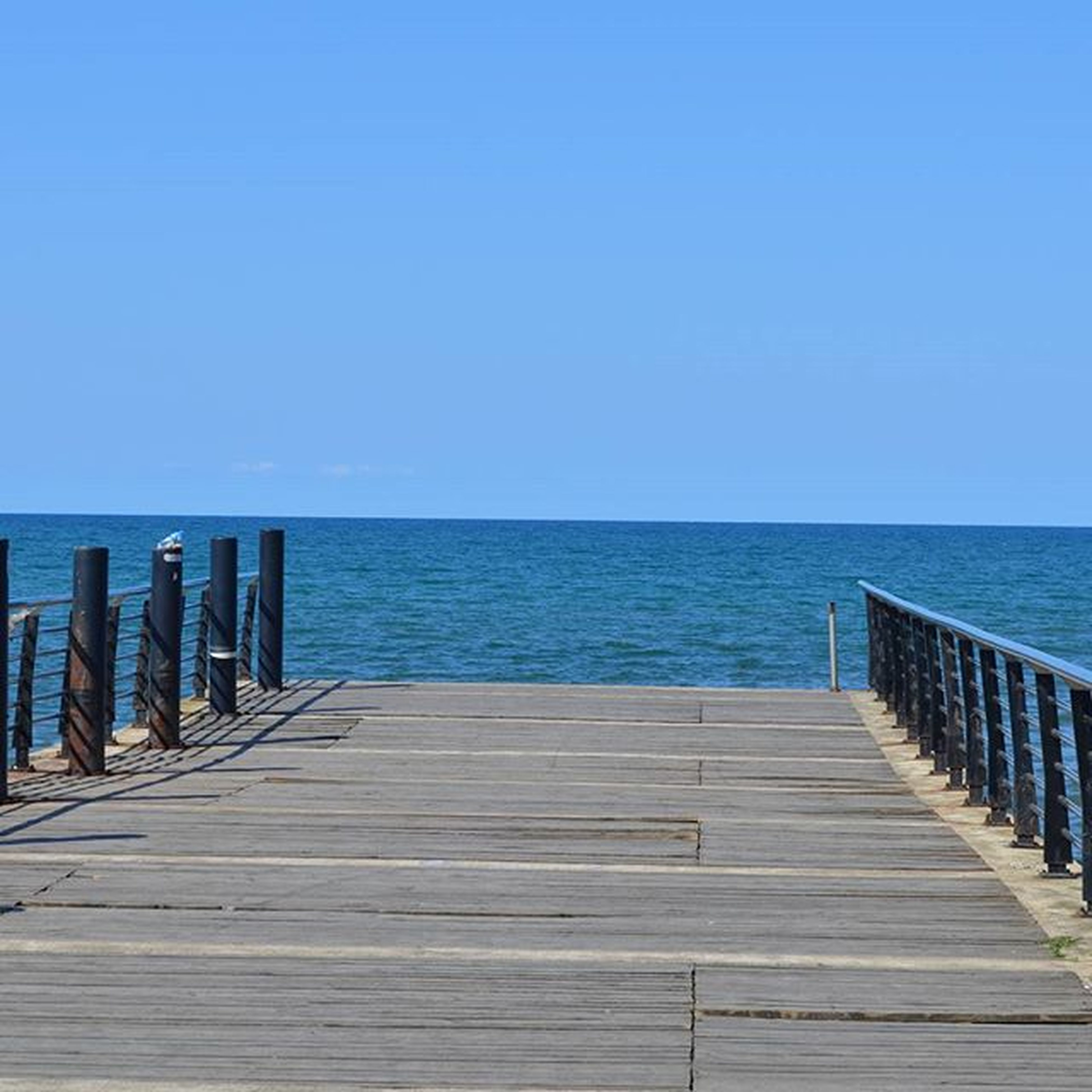 sea, water, horizon over water, clear sky, pier, blue, tranquil scene, tranquility, copy space, scenics, railing, wood - material, beauty in nature, jetty, nature, boardwalk, idyllic, wood, ocean, the way forward