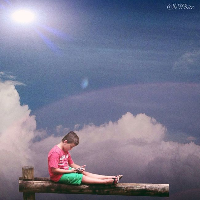 My son Riley playing his mums iPhone in the clouds