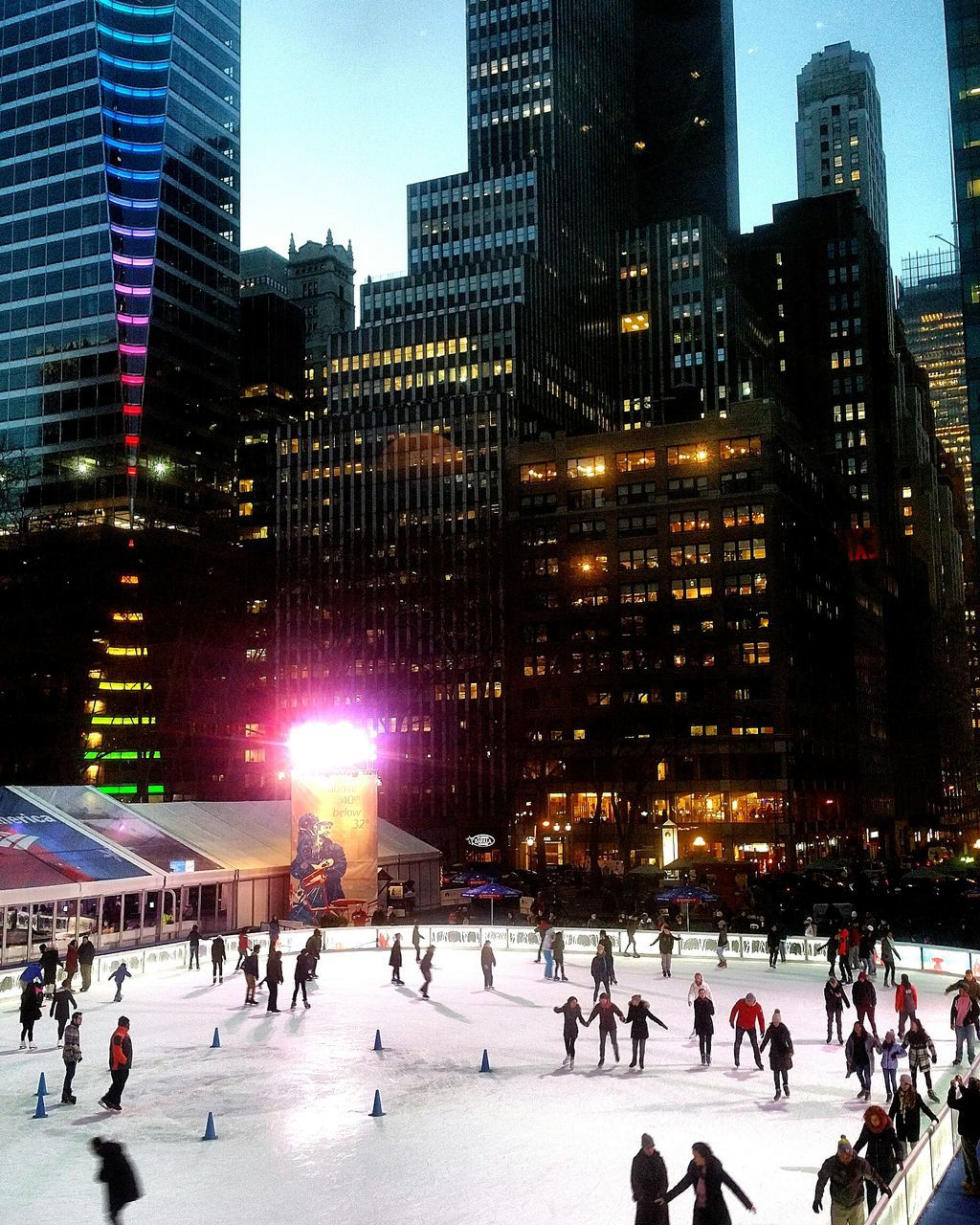 large group of people, architecture, building exterior, built structure, ice-skating, real people, city, ice rink, illuminated, city life, skyscraper, leisure activity, winter sport, skating, lifestyles, outdoors, travel destinations, men, modern, winter, cold temperature, women, night, crowd, cityscape, people