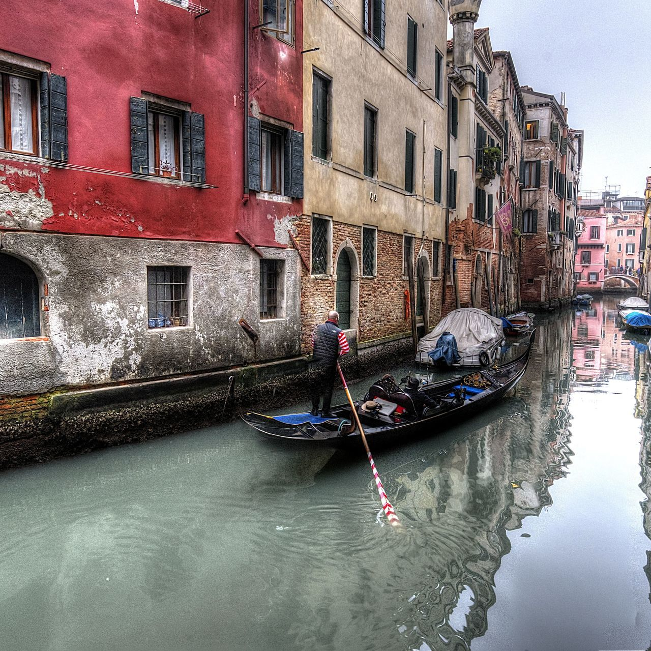 building exterior, architecture, built structure, canal, real people, nautical vessel, waterfront, transportation, mode of transport, day, window, water, outdoors, gondola, gondola - traditional boat, travel destinations, one person, moored, men, city, sky, people