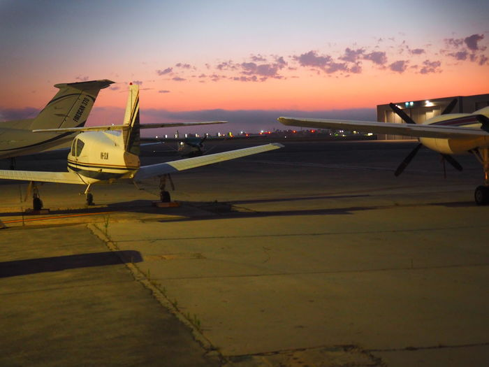 Aerospace Industry Air Vehicle Airplane Airport Airport Runway Dawn Sky Day Light Clouds No People Orange Sky Outdoors Sky Sunrise Sunset Transportation Travel The City Light