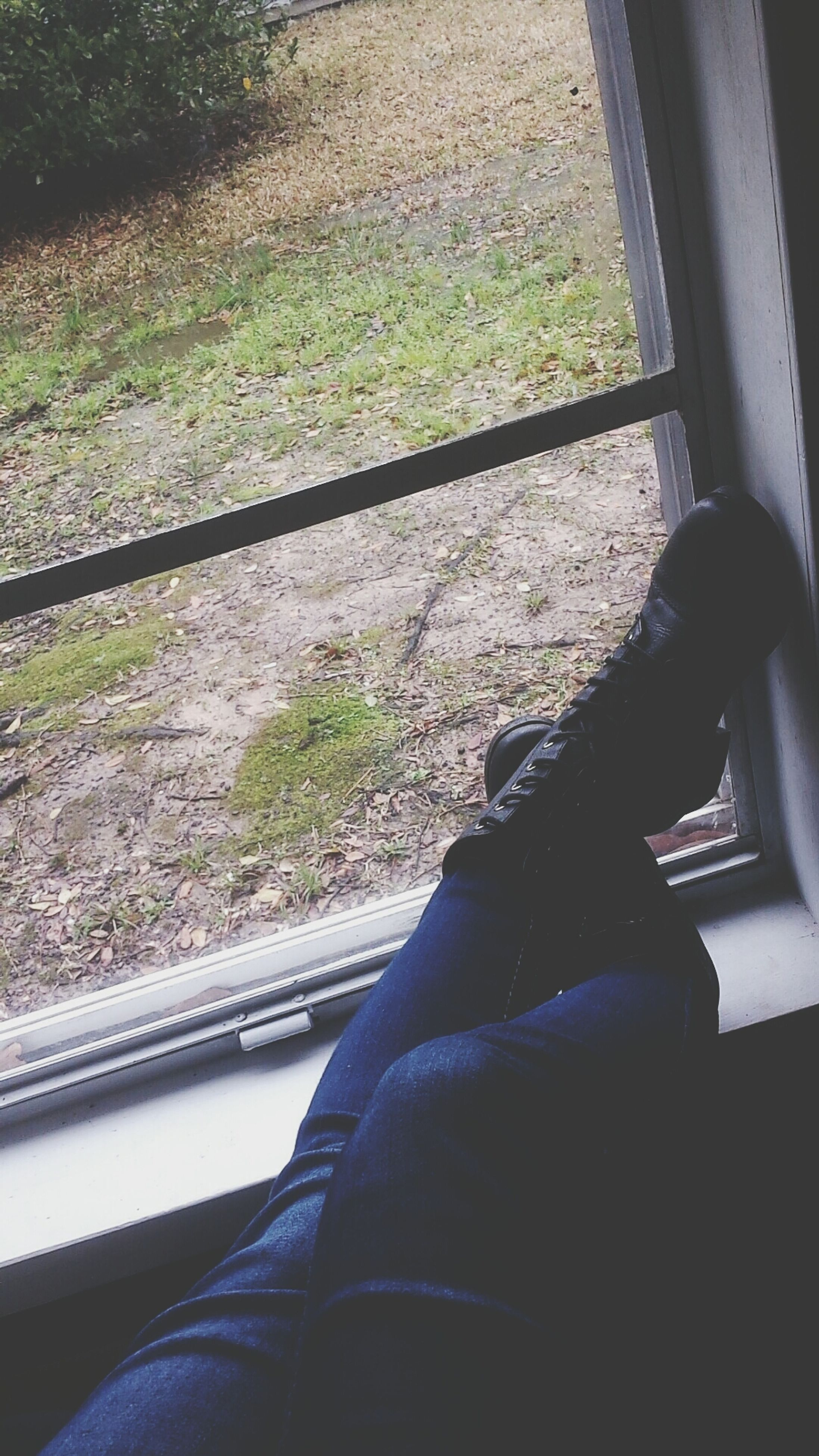 lifestyles, personal perspective, low section, sitting, person, leisure activity, men, relaxation, shoe, window, legs crossed at ankle, part of, day, casual clothing, jeans, technology, sunlight