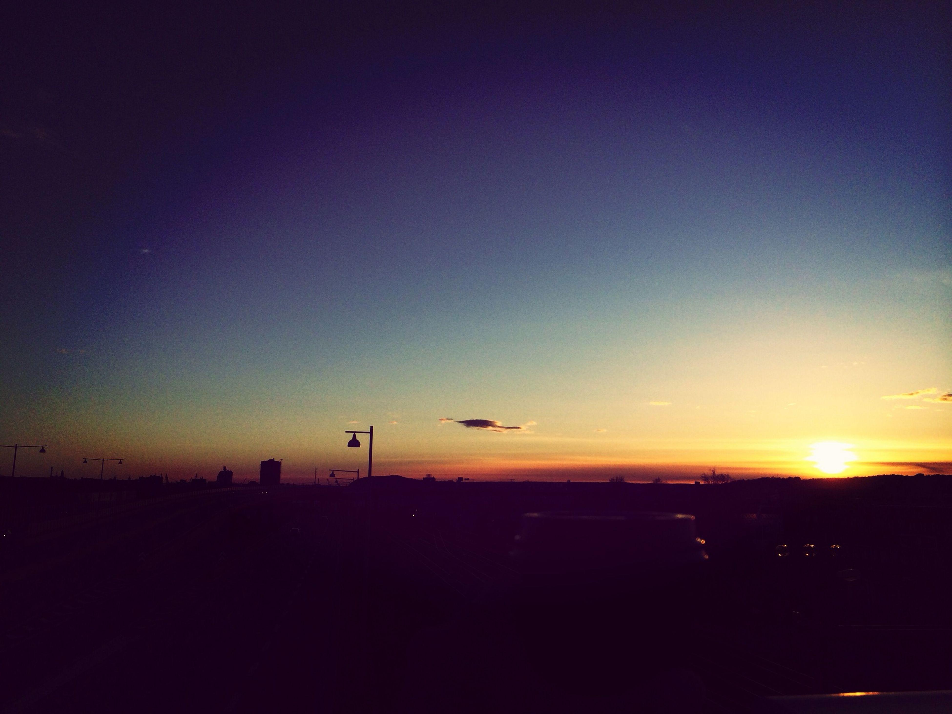 sunset, silhouette, copy space, orange color, scenics, landscape, sun, clear sky, transportation, tranquil scene, beauty in nature, tranquility, nature, sky, dusk, dark, mode of transport, idyllic, horizon over land, outdoors