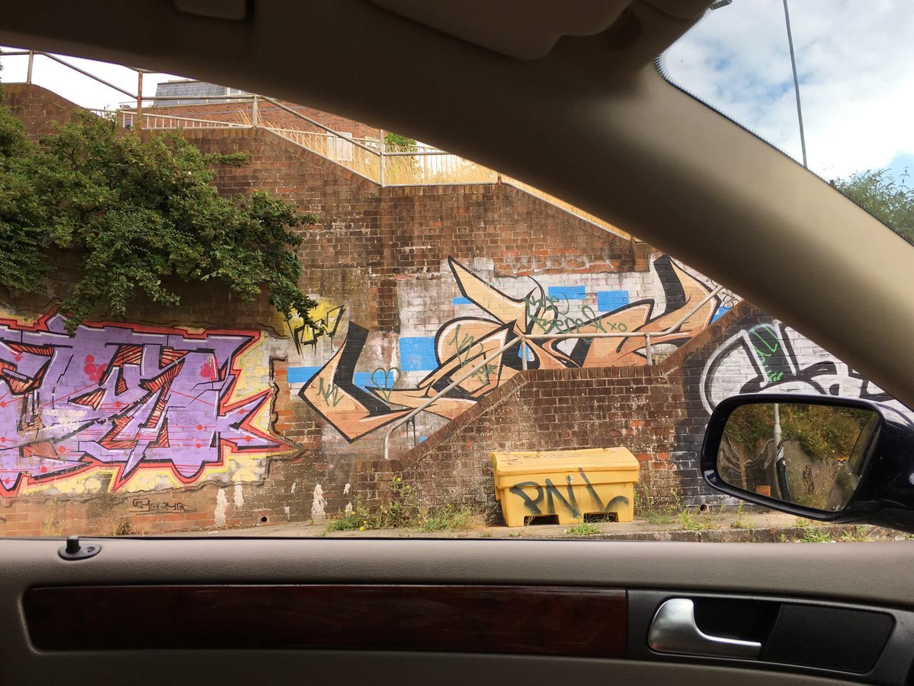 architecture, built structure, car, graffiti, text, land vehicle, transportation, mode of transport, day, building exterior, no people, window, tree, city, outdoors, sky