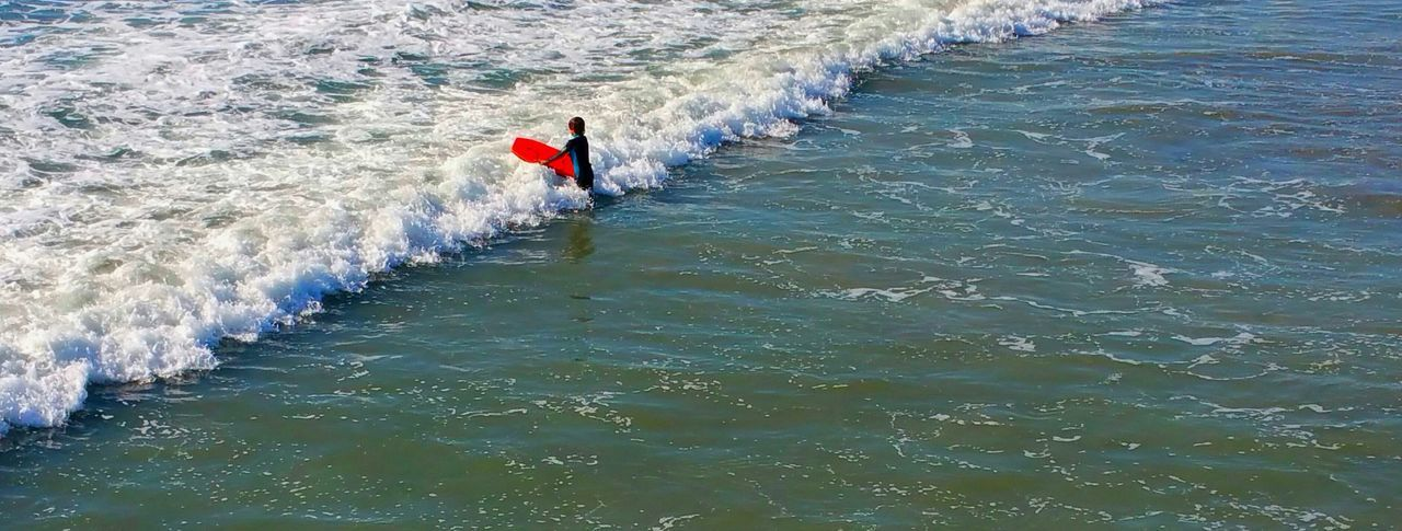 high angle view, water, one person, real people, day, leisure activity, motion, nature, sea, men, adventure, outdoors, lifestyles, full length, wave, one man only, beauty in nature, only men, young adult, adult, adults only, people