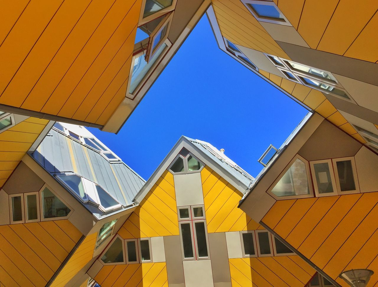 yellow, building exterior, architecture, built structure, low angle view, window, clear sky, day, outdoors, blue, no people, sunlight, sky, awning