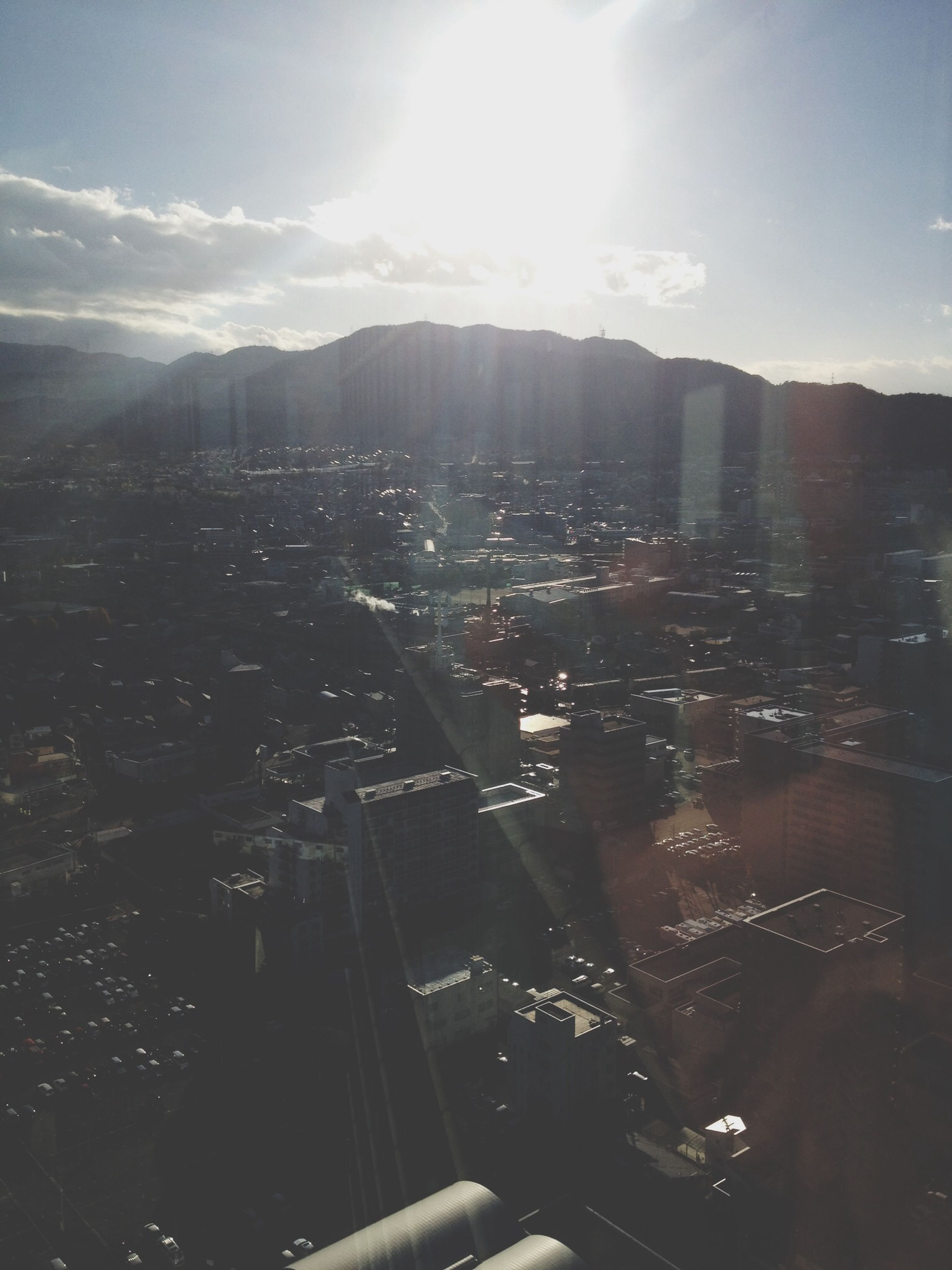 sunbeam, sun, building exterior, sunlight, sky, built structure, lens flare, architecture, cityscape, city, mountain, cloud - sky, high angle view, sunny, crowded, day, residential district, outdoors, aerial view, residential building