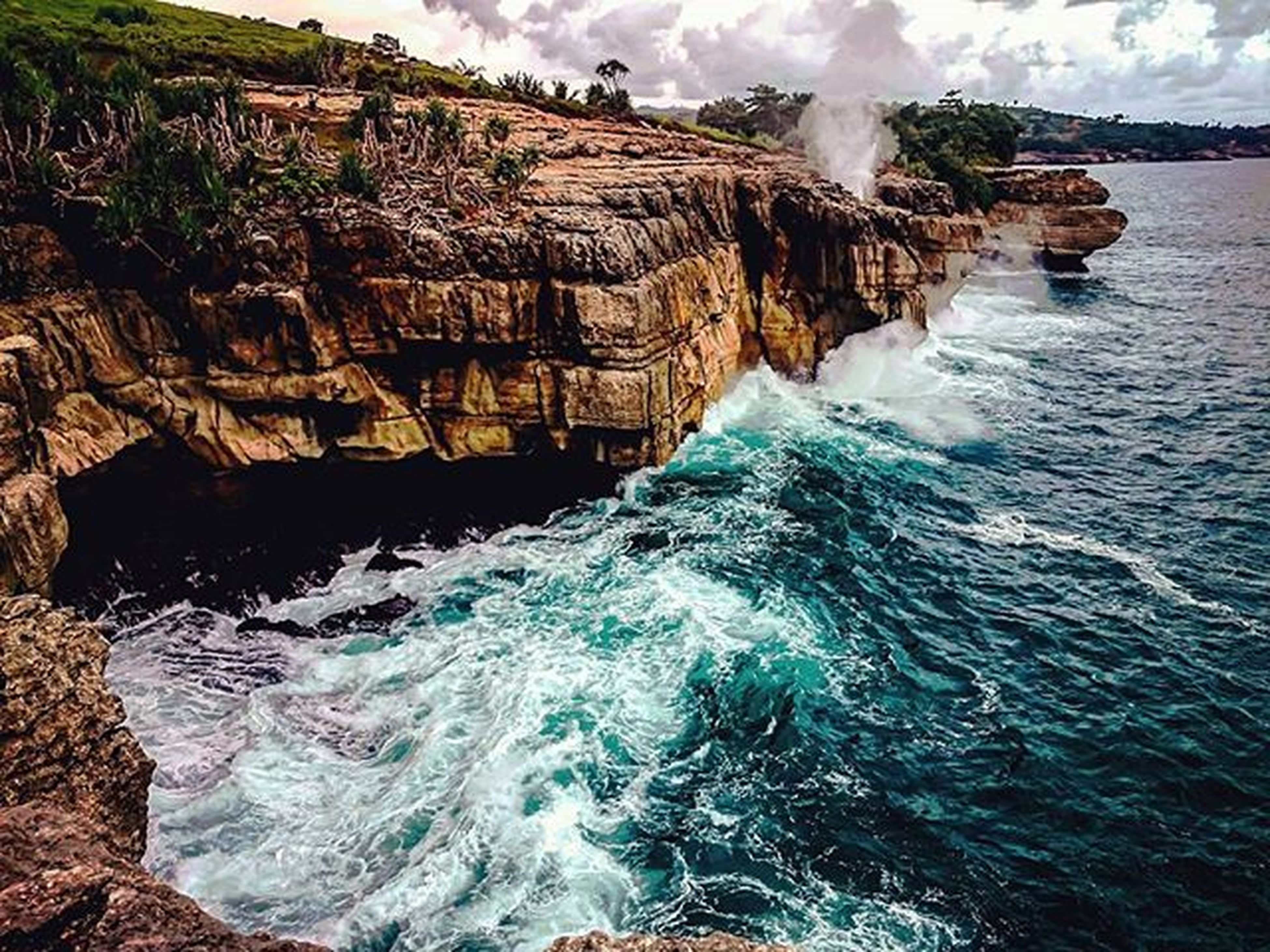 water, sea, rock - object, surf, wave, motion, waterfront, rock formation, beauty in nature, nature, scenics, rippled, splashing, high angle view, built structure, day, power in nature, flowing water, architecture, rock