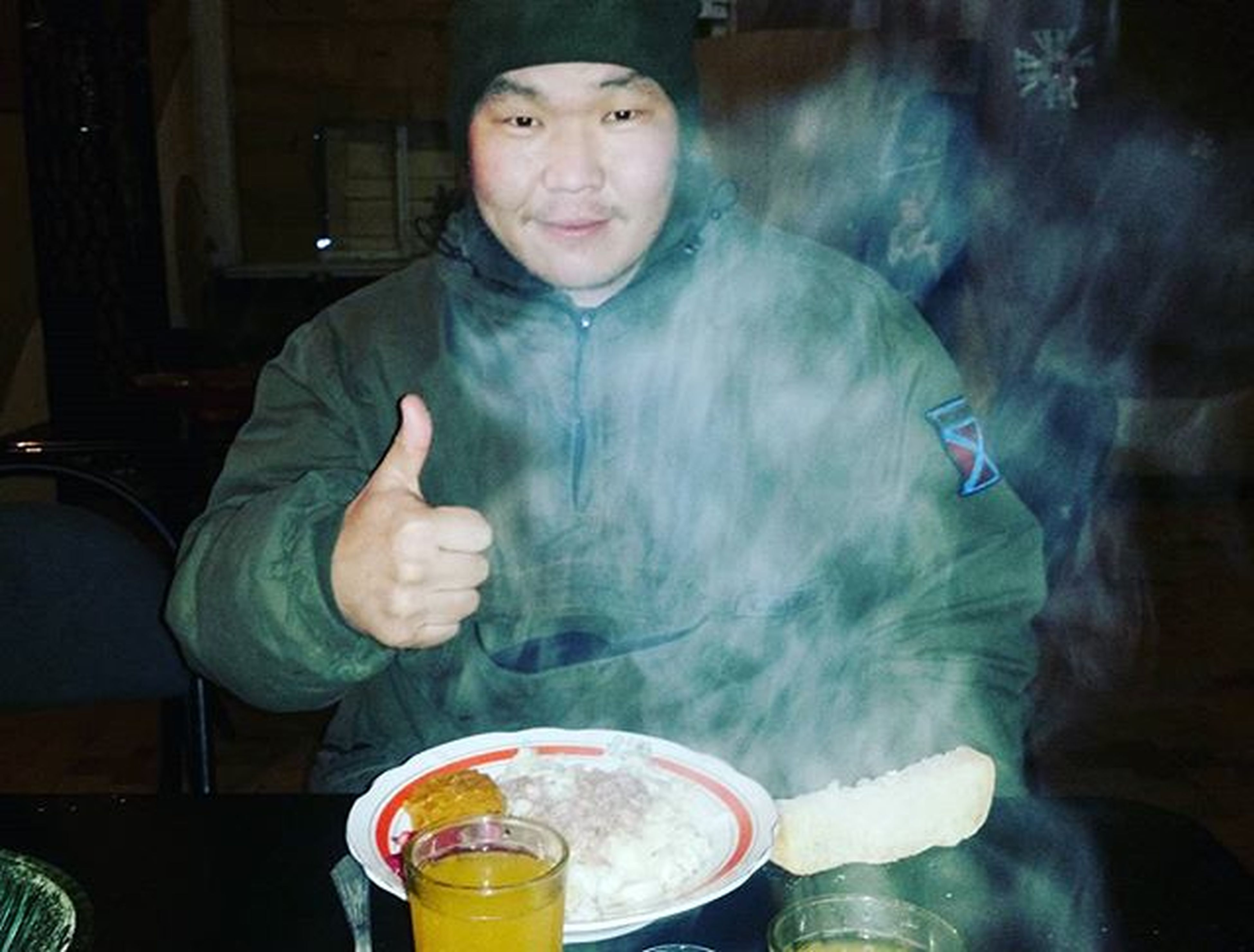 indoors, person, lifestyles, leisure activity, drink, young adult, refreshment, casual clothing, holding, waist up, water, front view, sitting, looking at camera, food and drink, table, three quarter length, reflection