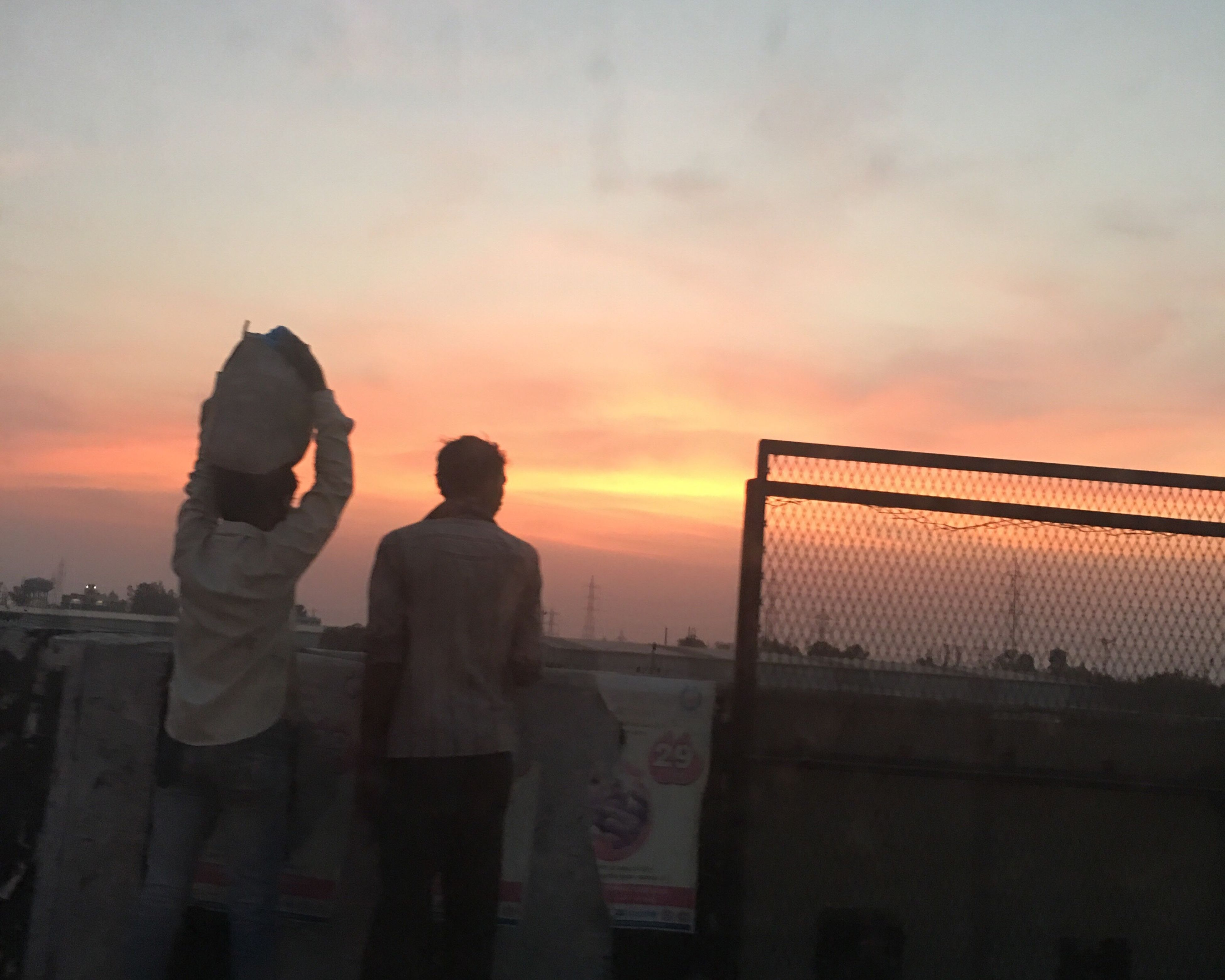 sunset, lifestyles, sky, standing, leisure activity, orange color, men, silhouette, cloud - sky, rear view, railing, built structure, three quarter length, full length, architecture, person, casual clothing
