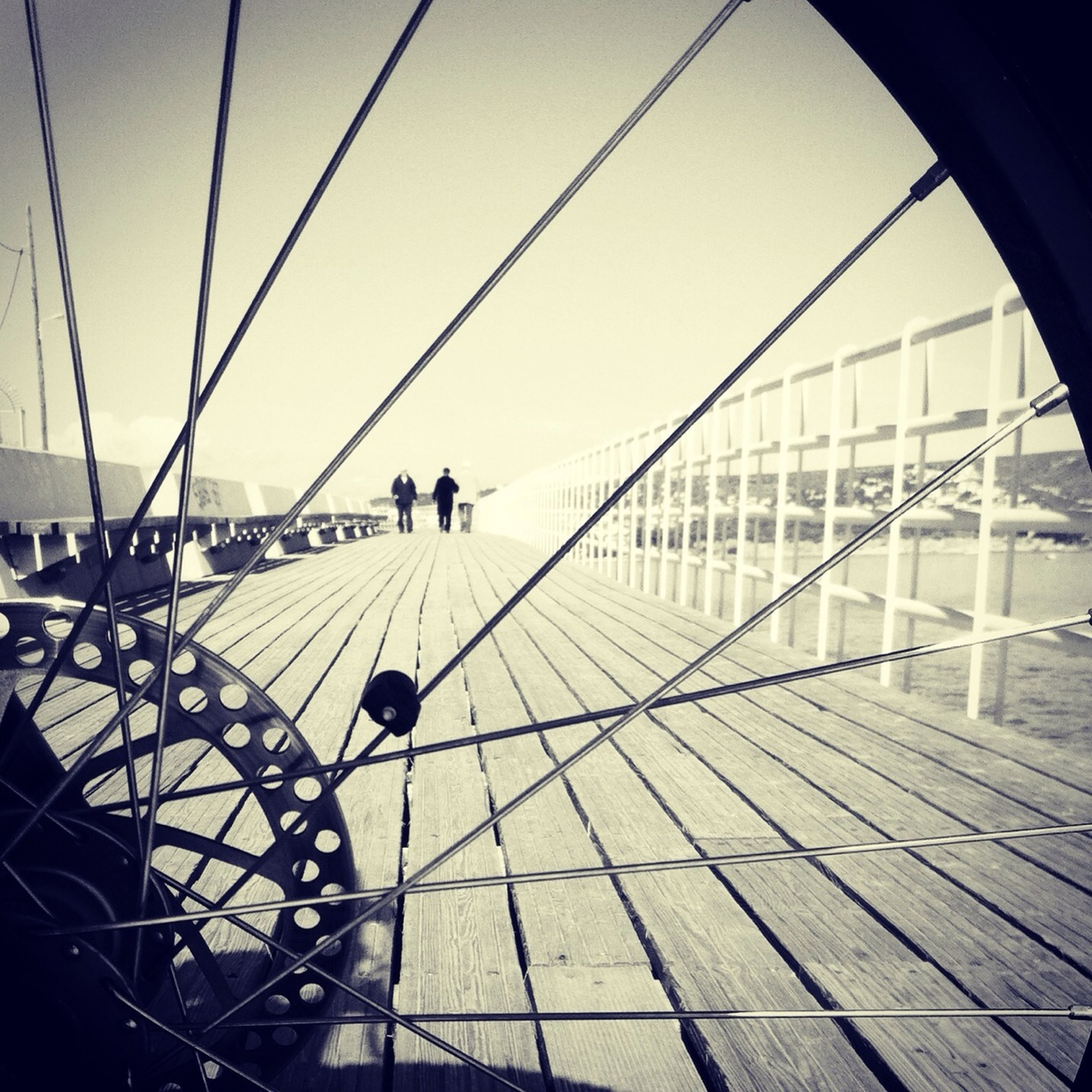 men, transportation, leisure activity, lifestyles, bicycle, mode of transport, travel, person, walking, sunlight, built structure, architecture, railing, shadow, clear sky, medium group of people, sky