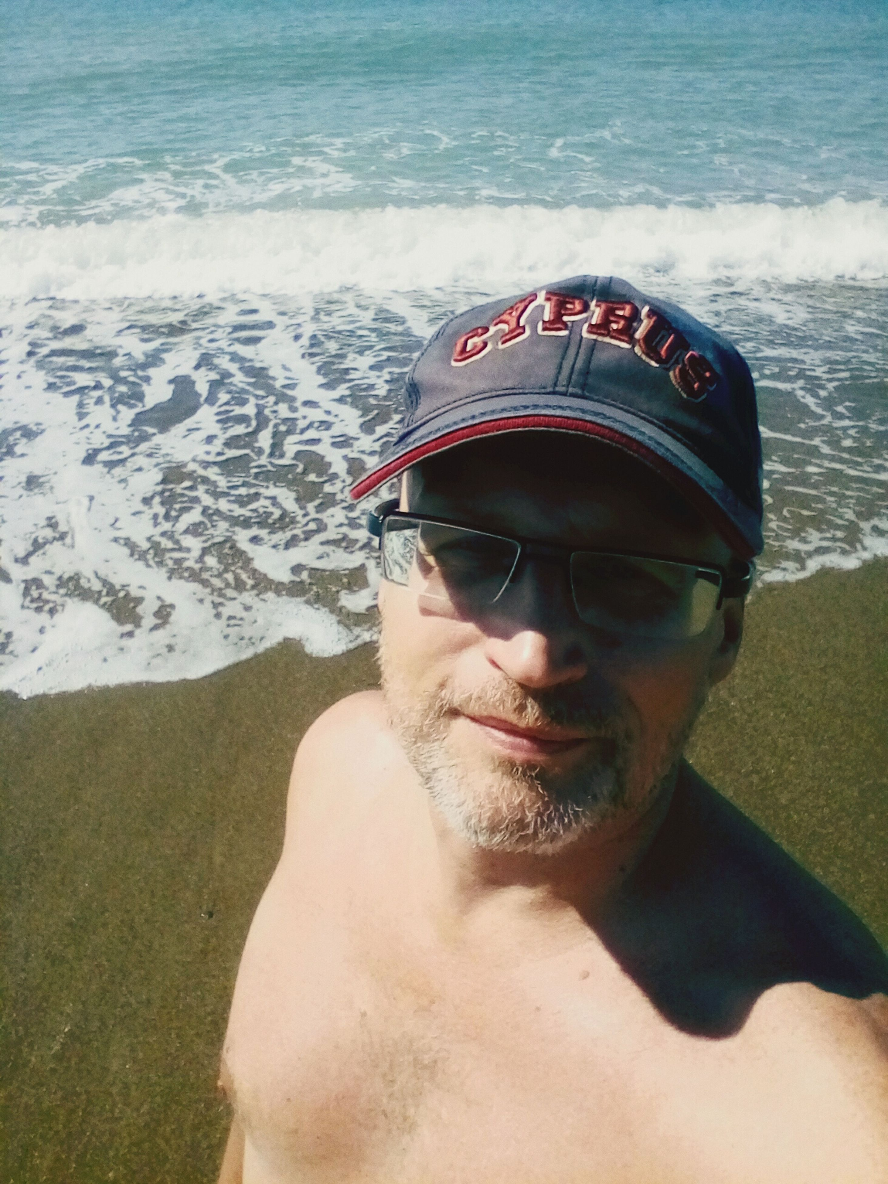 sea, real people, water, beach, shore, sunglasses, one person, sand, lifestyles, mid adult men, leisure activity, day, outdoors, portrait, looking at camera, nature, cap, young adult, wave, close-up, mammal