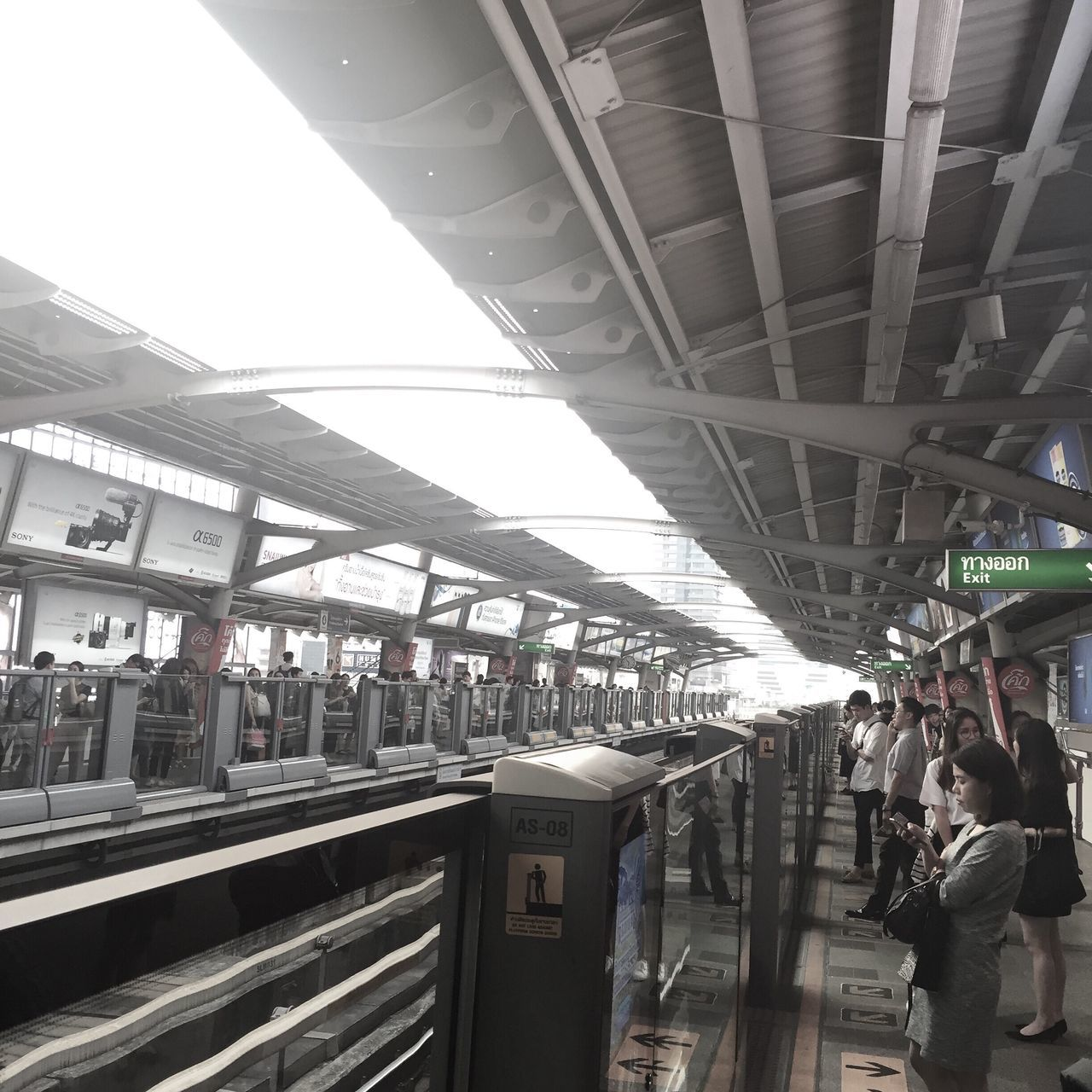 transportation, real people, public transportation, connection, architecture, built structure, men, lifestyles, mode of transport, railroad station platform, train - vehicle, railroad station, city life, bridge - man made structure, city, journey, large group of people, commuter, standing, women, day, indoors, people, adult