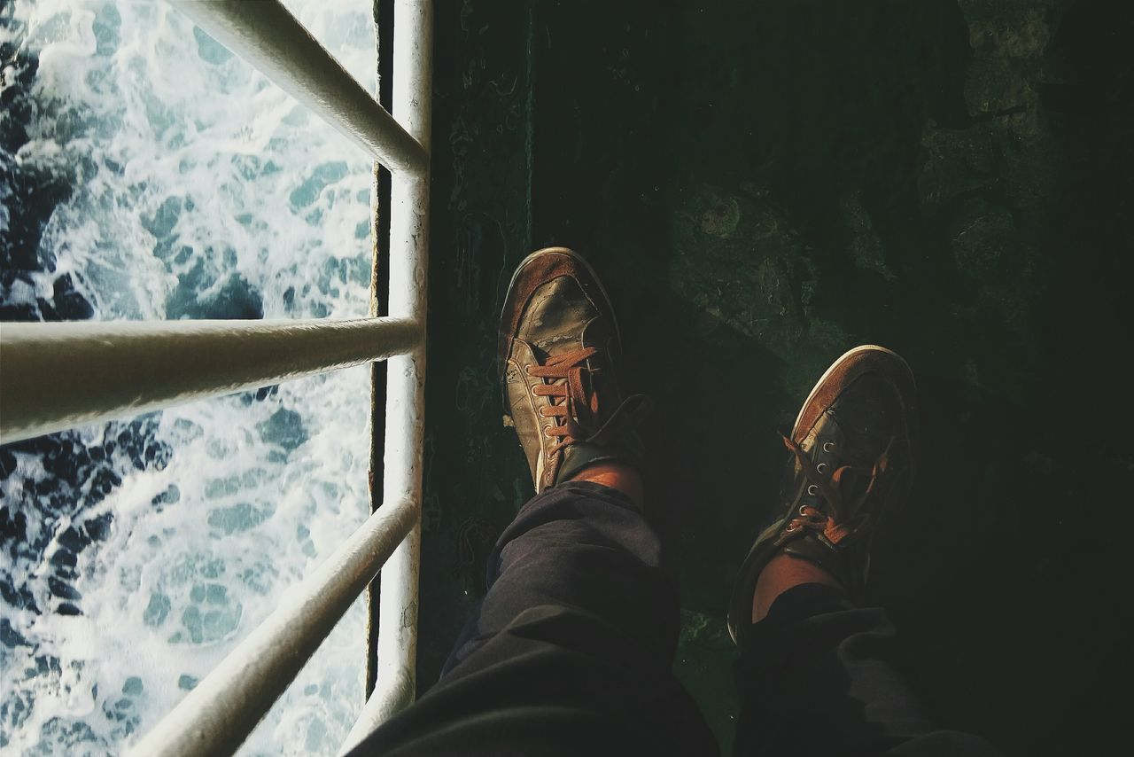 human leg, low section, personal perspective, human body part, shoe, real people, leisure activity, one person, lifestyles, day, standing, men, close-up, water, canvas shoe, outdoors, people