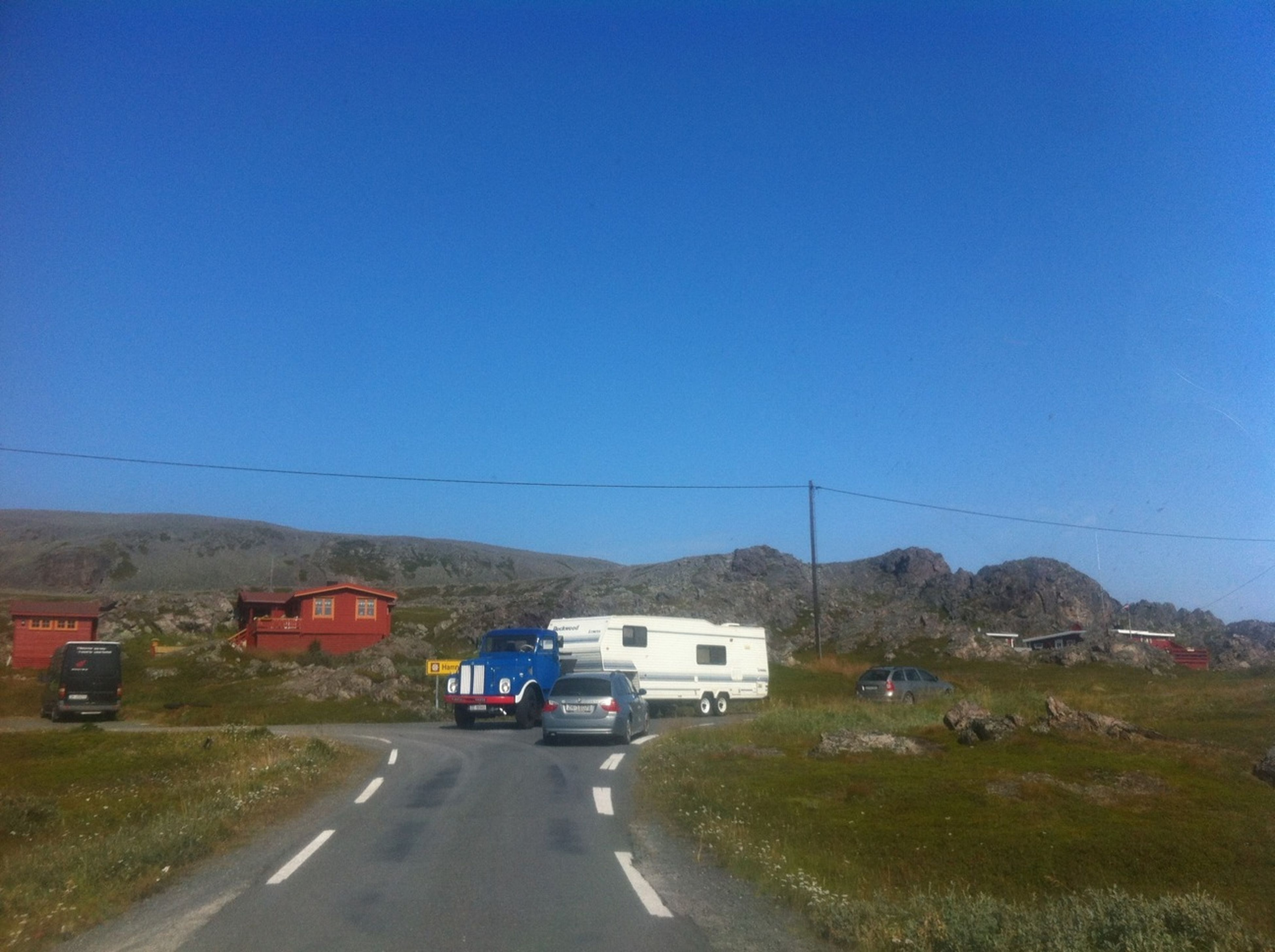 transportation, road, land vehicle, car, clear sky, mode of transport, blue, copy space, the way forward, road marking, power line, street, electricity pylon, mountain, country road, connection, sky, landscape, on the move, diminishing perspective