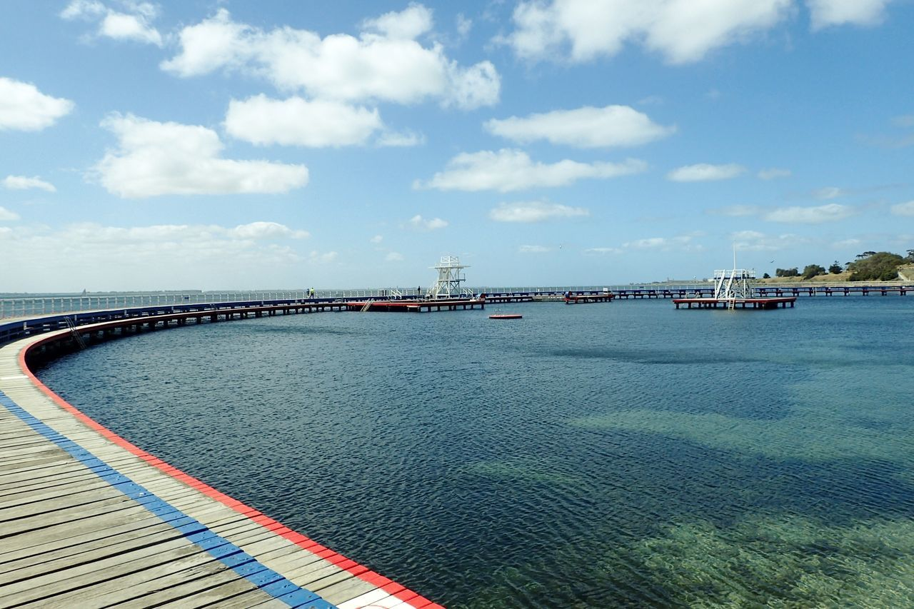 Bridge Over Sea Against Sky During Sunny Day