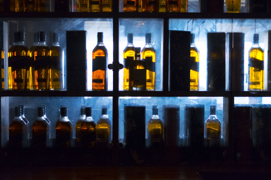 Alcohol Bar - Drink Establishment Black Background Blue Choice Happy Hour Hard Liquor Illuminated In A Row Indoors  Laboratory Large Group Of Objects Liqueur Night No People Variation Whiskey