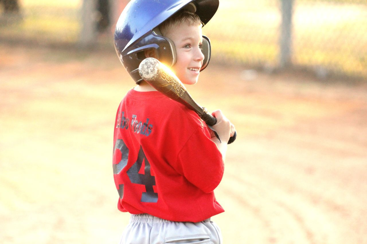 childhood, boys, headwear, one person, real people, elementary age, helmet, smiling, casual clothing, happiness, leisure activity, lifestyles, outdoors, sports helmet, standing, day, baseball helmet, people