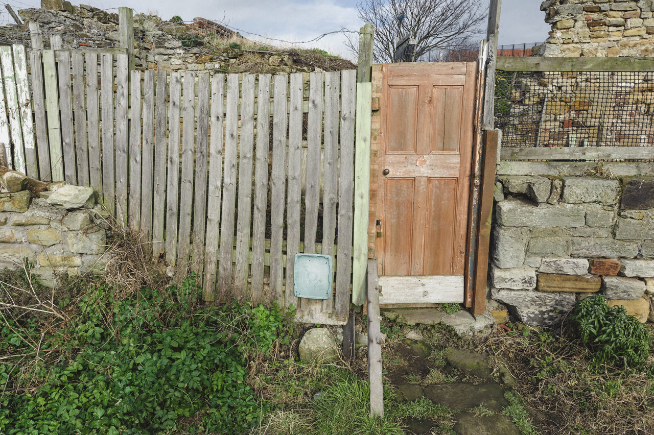 An amalgamation of materials used together to make a fence with a door for access Brick Walls Built Structure Catflap Day Door Fence Gate Grass No People Outdoors Rural Rural Scene Stone Wall Wall Whitby Yorkshire