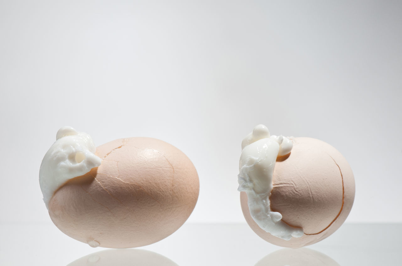 Two boiled cracked eggs shells with egg white outside, whole eggs lying on glass and grey background in horizontal orientation, nobody, studio shot. Albumen Boiled Break Broken Crack Cracked Egg Eggs Eggshell Food Fragility Glair Glaire No People Rupture Studio Shot