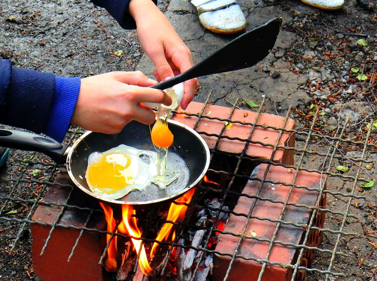 Ash Barbecue Barbecue Grill Burning Camping Close-up Day Eggs Eier Feuer Fire Pit Flame Food Food And Drink Freshness Heat - Temperature High Angle View Holding Human Body Part Human Hand Leisure Activity Outdoors P Preparation  Real People