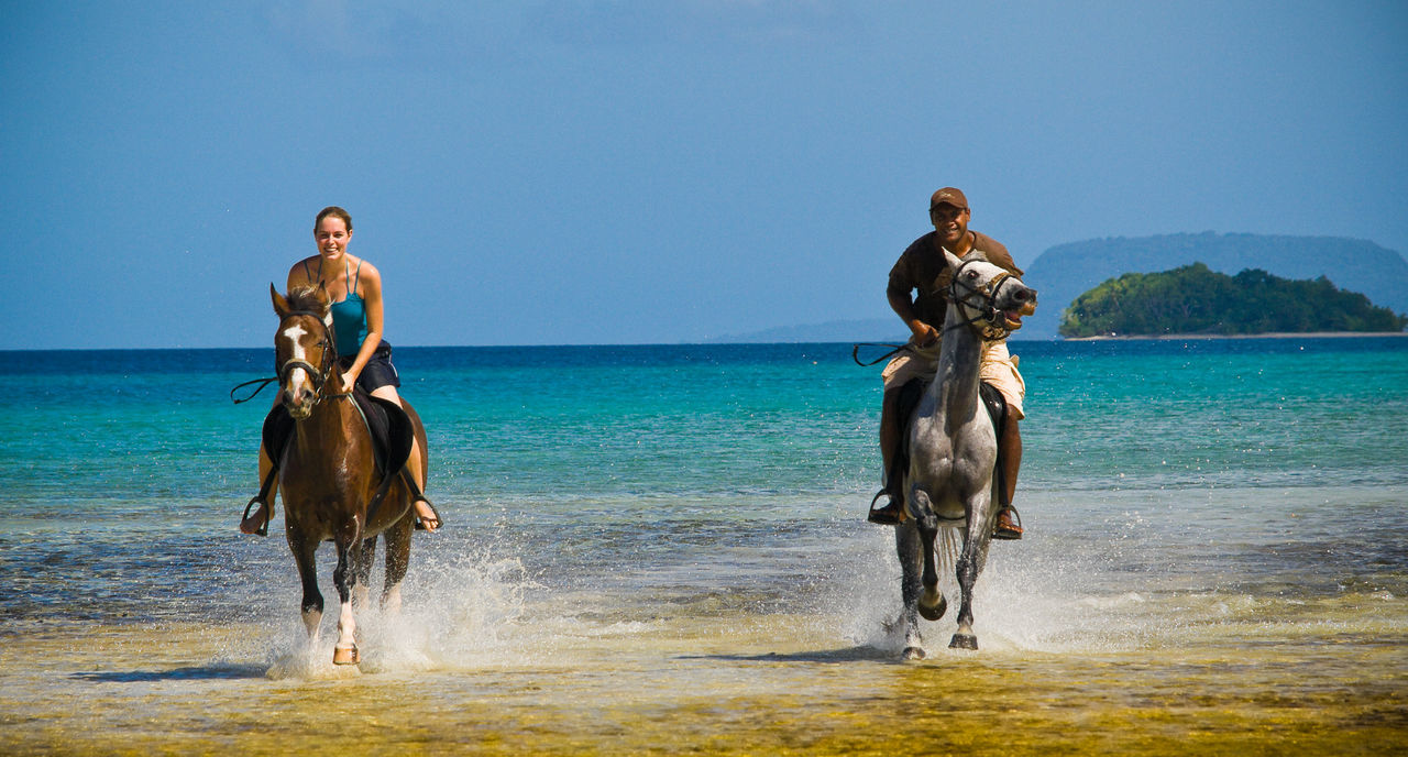 riding, outdoors, sea, domestic animals, horseback riding, real people, nature, mammal, transportation, water, day, full length, lifestyles, speed, clear sky, men, leisure activity, sky, beauty in nature, scenics, one person, young adult, people