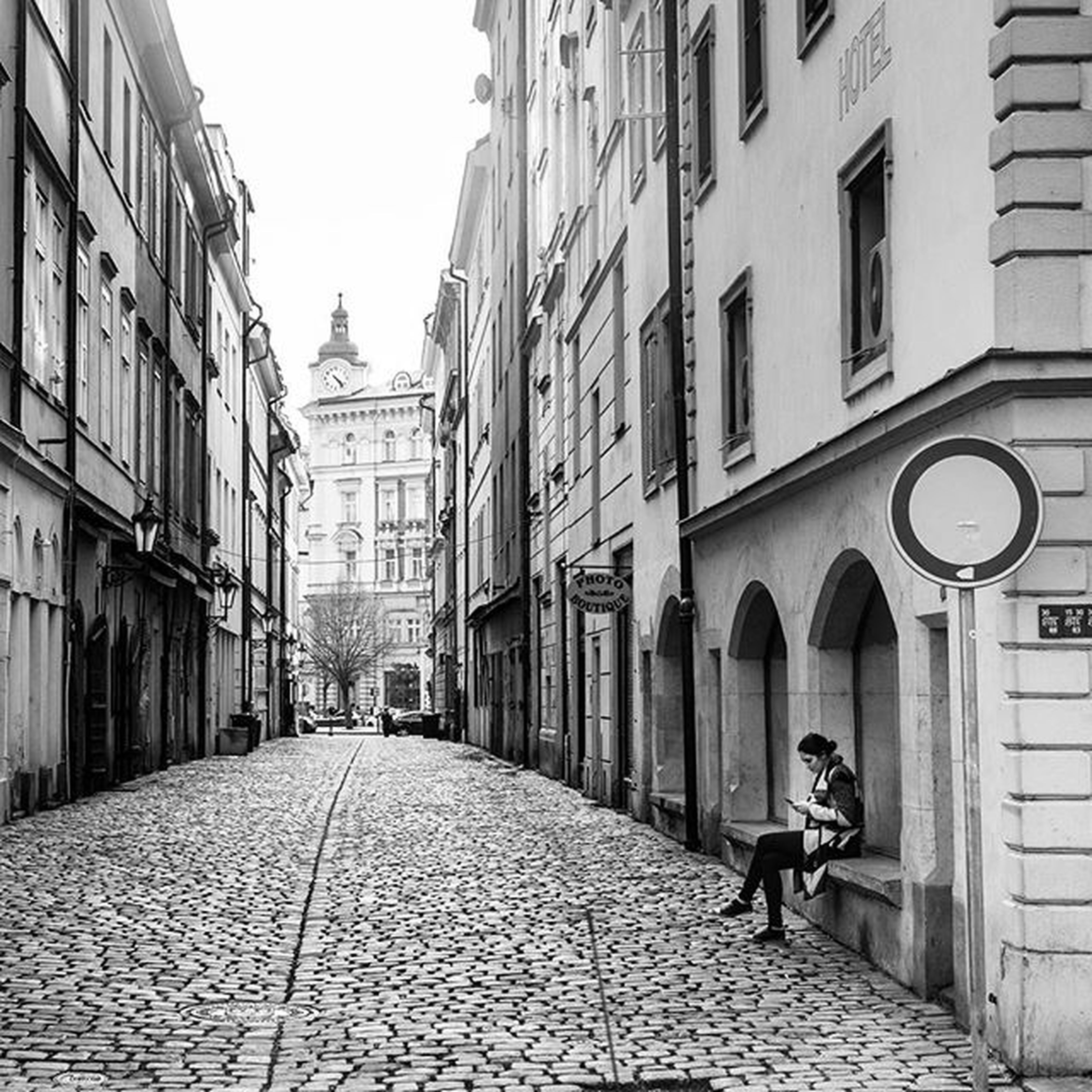 building exterior, architecture, built structure, cobblestone, the way forward, street, walking, city, men, building, diminishing perspective, rear view, residential structure, residential building, full length, footpath, lifestyles, arch