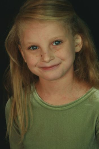 Black Background Blond Hair Blue Eyes Child Childhood Children Only Close-up Day Elementary Age Freckle Front View Girls Headshot Indoors  Innocence Looking At Camera One Girl Only One Person People Portrait Pre-adolescent Child Real People Single Smiling