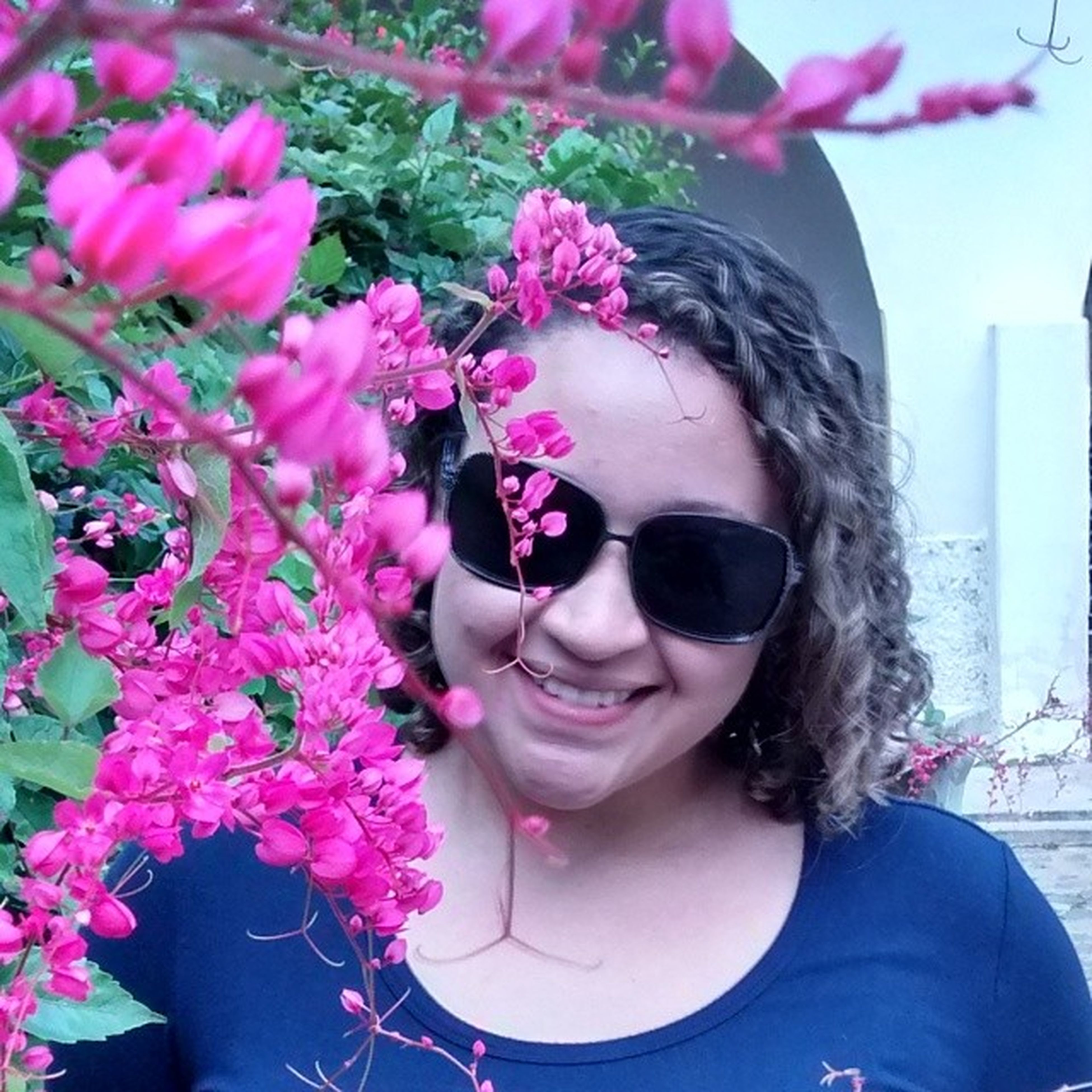 flower, headshot, person, portrait, looking at camera, lifestyles, leisure activity, young adult, front view, young women, close-up, smiling, pink color, childhood, girls, day, casual clothing, focus on foreground