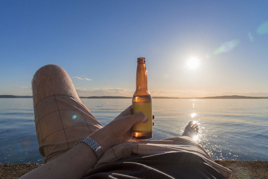 Personal perspective man holding beer bottle while laying by the sea as the sun is setting. Alcohol Alcohol Beach Beauty In Nature Beer Bottle Drink Holding Horizon Over Water Human Body Part Human Leg Leisure Activity Lifestyles Mens Health Nature Outdoors Personal Perspective Phalic Refreshment Sea Sky Sun Sunlight Sunset Water