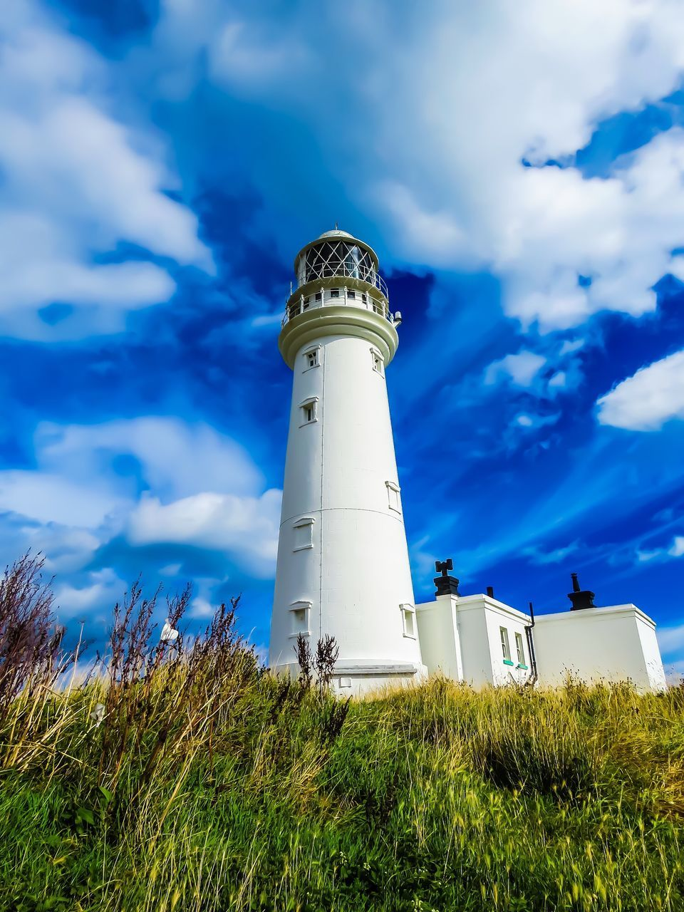 lighthouse, cloud - sky, sky, low angle view, guidance, day, grass, no people, outdoors, architecture, nature