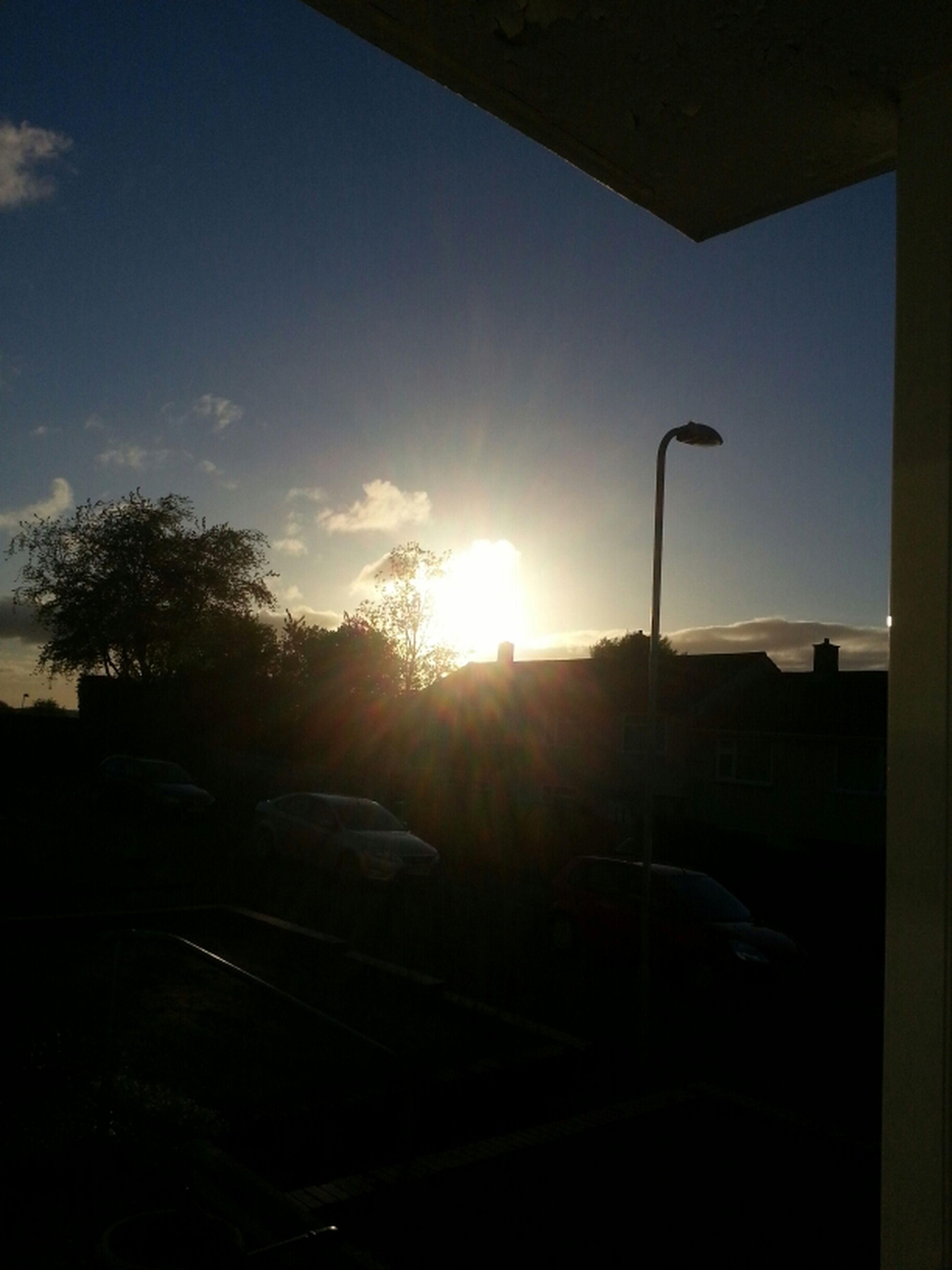 sun, silhouette, sunlight, sunset, sunbeam, car, street light, tree, sky, transportation, land vehicle, built structure, lens flare, architecture, street, building exterior, road, mode of transport, clear sky, window