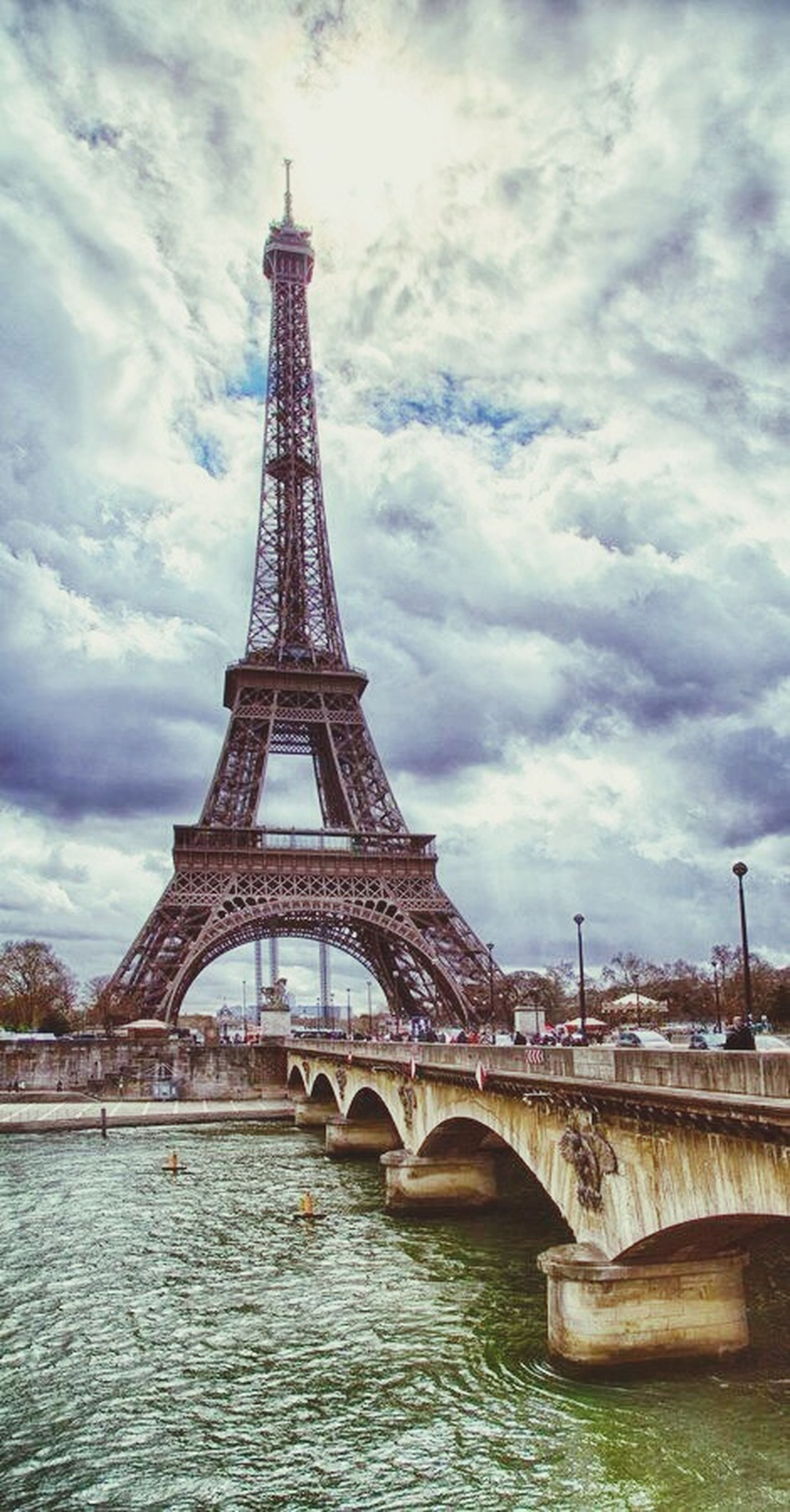 architecture, built structure, connection, bridge - man made structure, sky, cloud - sky, engineering, water, river, international landmark, cloudy, famous place, travel destinations, transportation, low angle view, travel, tourism, eiffel tower, cloud, capital cities