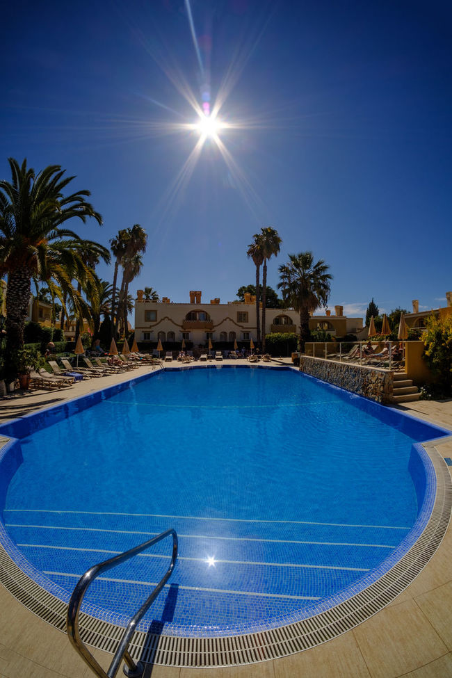 Swimming Pool Blue Sun Sunlight Palm Tree Poolside Lens Flare Tourist Resort Sky Summer Xpro2 Carvoeiro Fujifilm Algarve Fujifilm_xseries Portugal X-PRO2 Photography Travel Destinations Xseries Samyang8mm Samyang Pestana