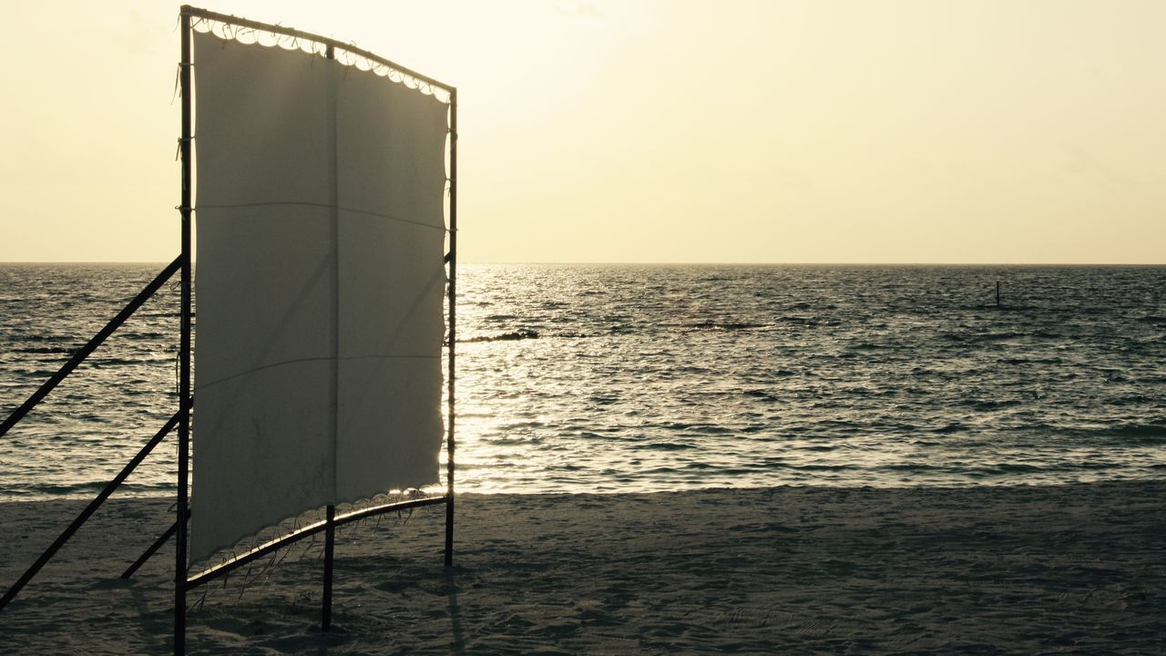 cinema screen at the beach in sunset Beach Beauty In Nature Canvas Cinema Construction Enjoying Life Evening Sky Fun Horizon Over Water Leisure Activity Maldives Movies Nature Nightlife No People Open Air Outdoors Reflection Sand Scenics Screen Sea Sky Sunset Water