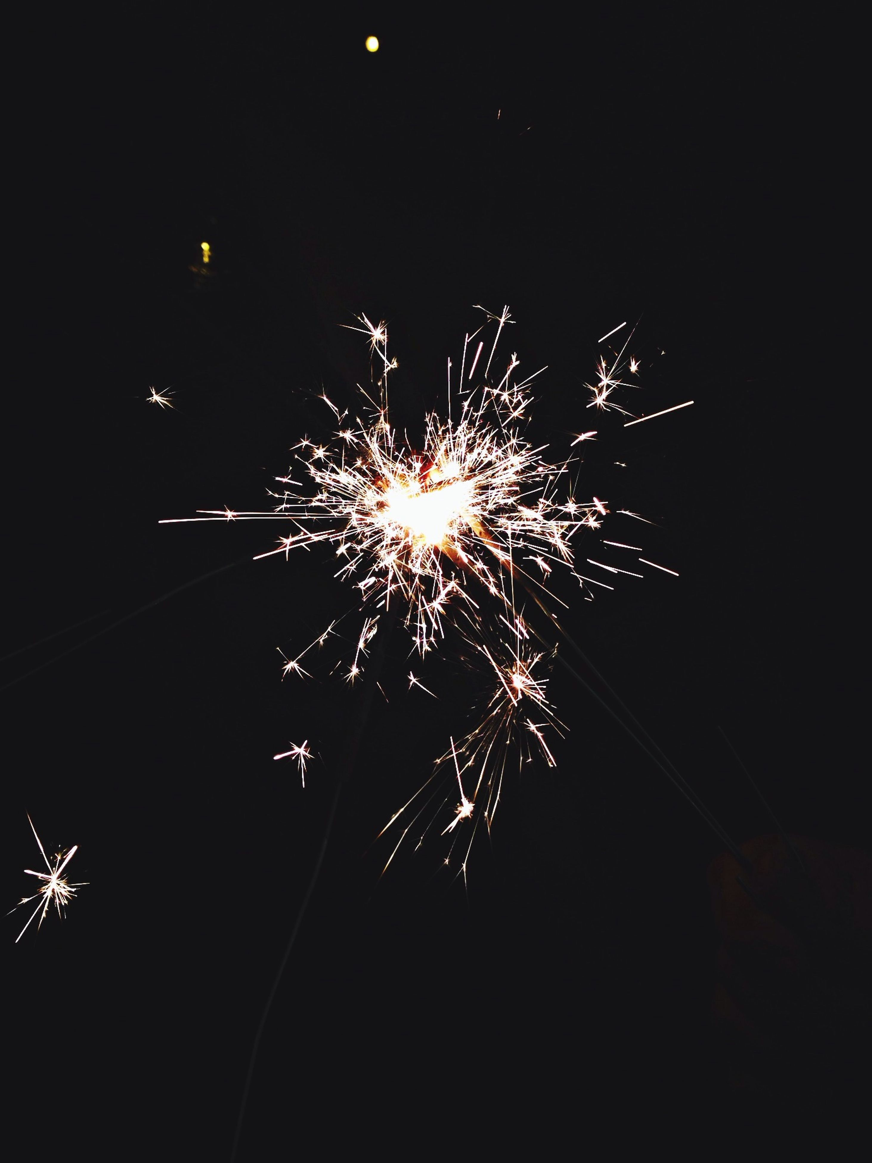 night, firework display, exploding, illuminated, celebration, firework - man made object, long exposure, arts culture and entertainment, low angle view, motion, sparks, glowing, event, firework, entertainment, blurred motion, sky, fire - natural phenomenon, celebration event, outdoors