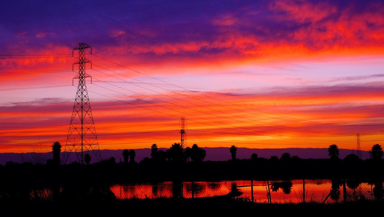 Silhouette Trees And Electricity Pylon Against Orange Cloudy Sky