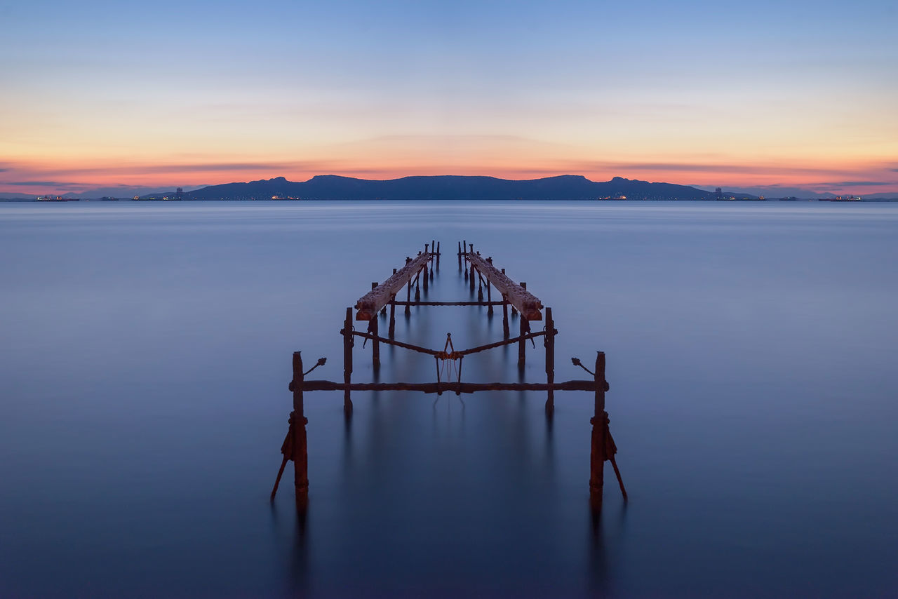 The remains of a wooden dock during sunset Blue Dock Ellada  Greece Hellas Incomplete Island Lake Landscape Minimal Minimalistic Mountain Mountains Ocean Peaceful Pier Pond Remains Ruins Sea Sky Sunset Water Wreck Wrecked