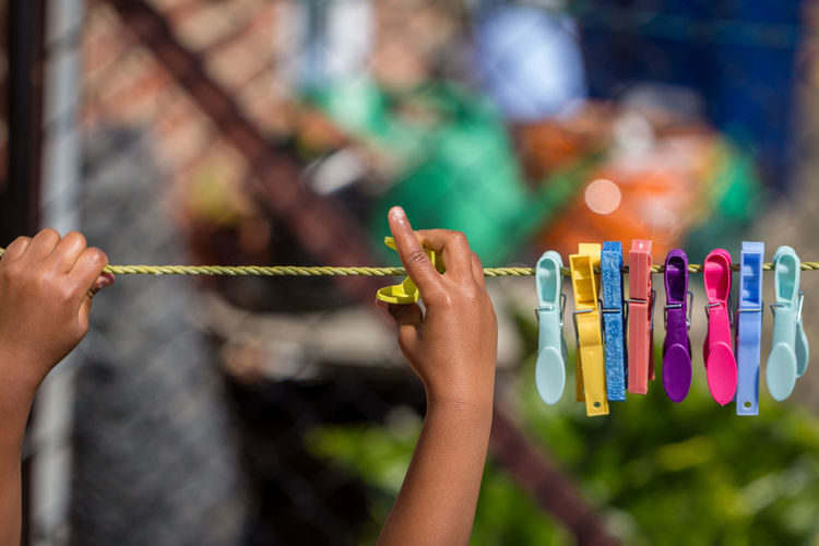 Close-up Multi Colored African Outdoors African American Afro Caribbean Garden Colorful Clothes Pegs Pegs Rope Girl Human Hand Hanging String Colourful Focus On Foreground One Person Child People Person Of Color Person Of Colour Peg Clothes Peg Washing Line