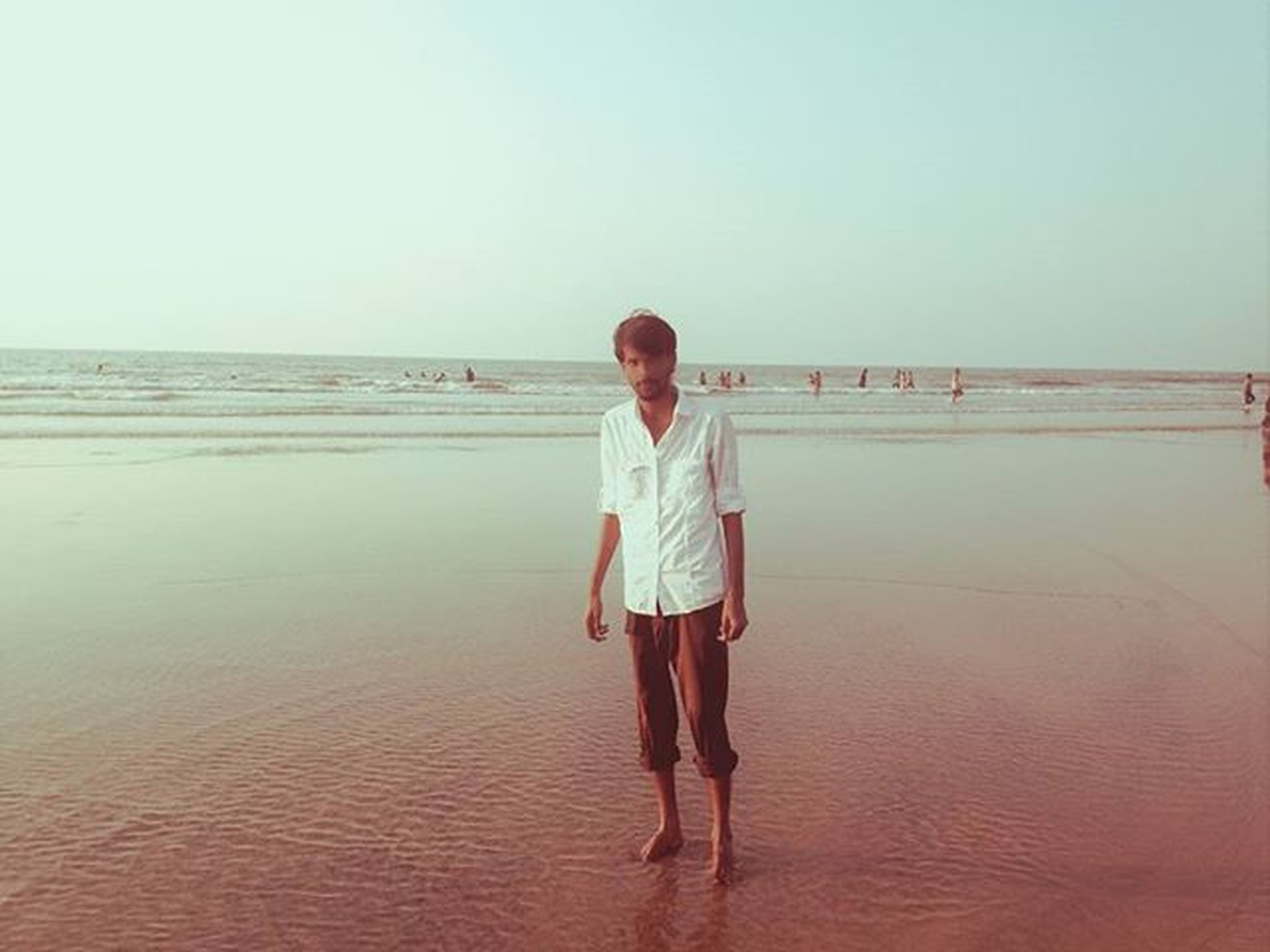 sea, water, full length, horizon over water, rear view, copy space, clear sky, standing, lifestyles, casual clothing, leisure activity, beach, walking, tranquility, tranquil scene, young adult, nature, person