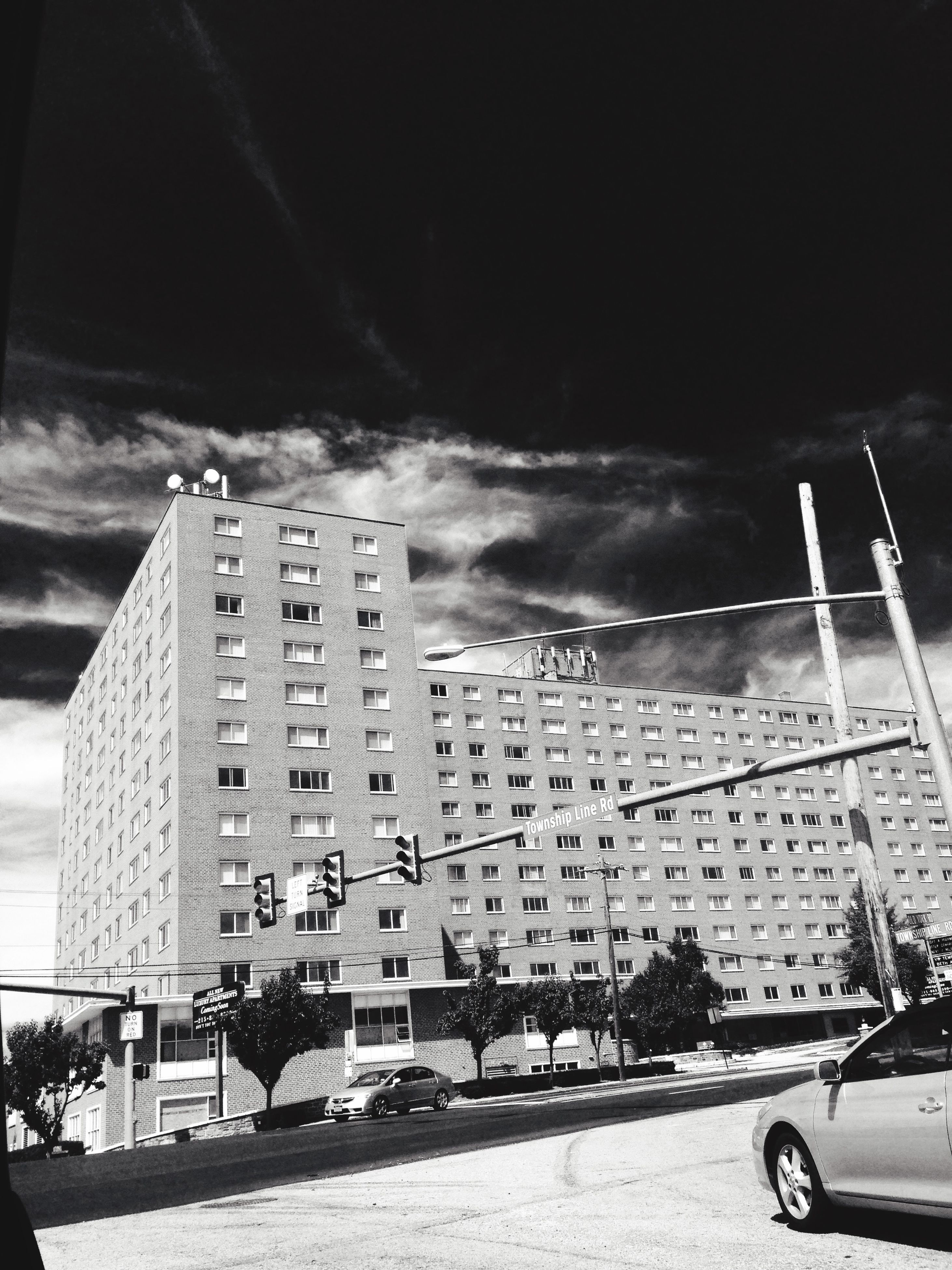 building exterior, architecture, built structure, sky, city, transportation, mode of transport, cloud - sky, land vehicle, road, street, outdoors, car, city life, sunlight, skyscraper, day, street light, high angle view, tall - high