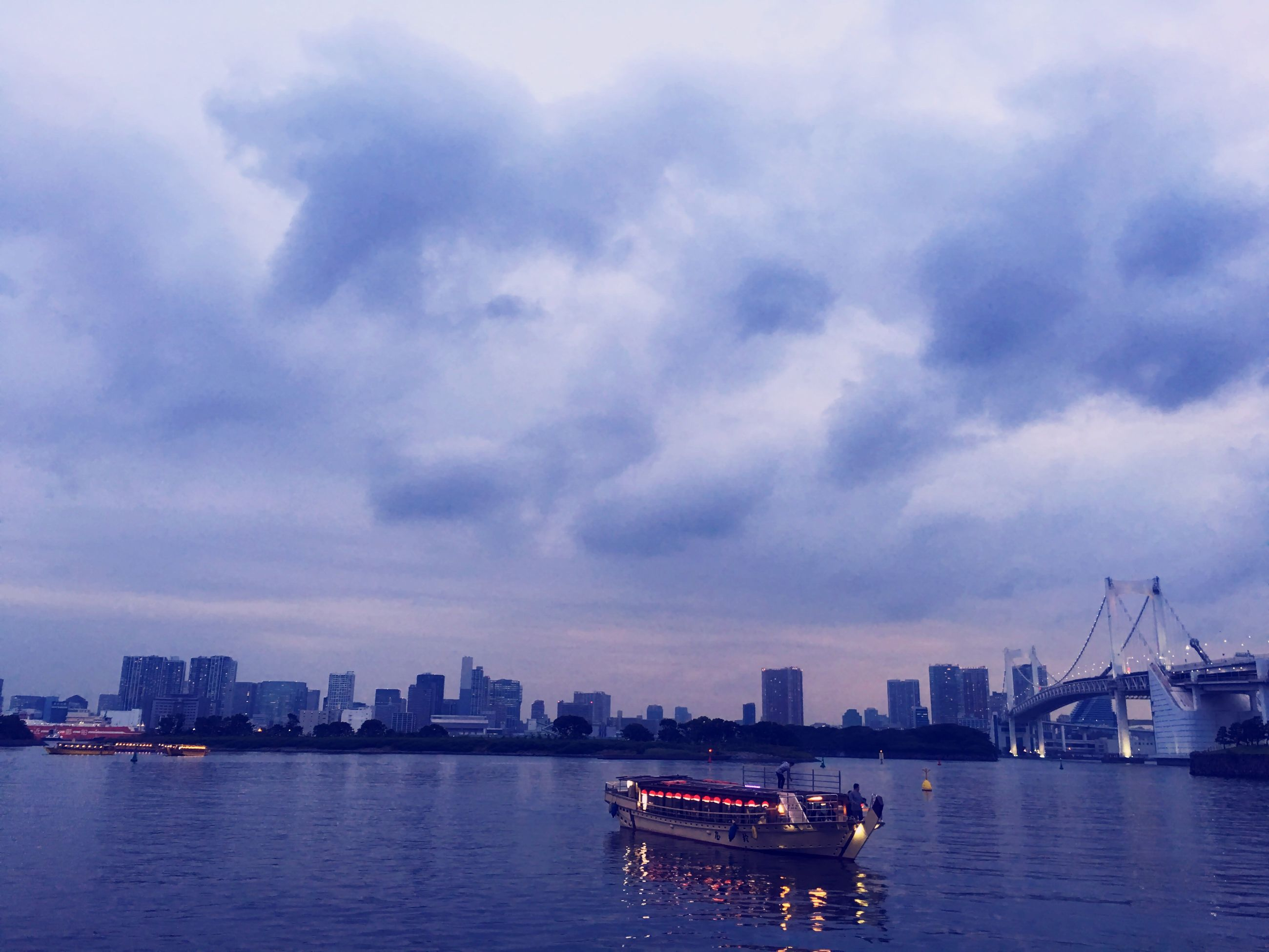 water, nautical vessel, transportation, city, waterfront, boat, mode of transport, building exterior, architecture, built structure, sky, cloud - sky, river, tranquil scene, growth, tranquility, sea, urban skyline, calm, day, skyscraper, outdoors, scenics, nature, city life, cloudy, no people, tall - high, beauty in nature, development