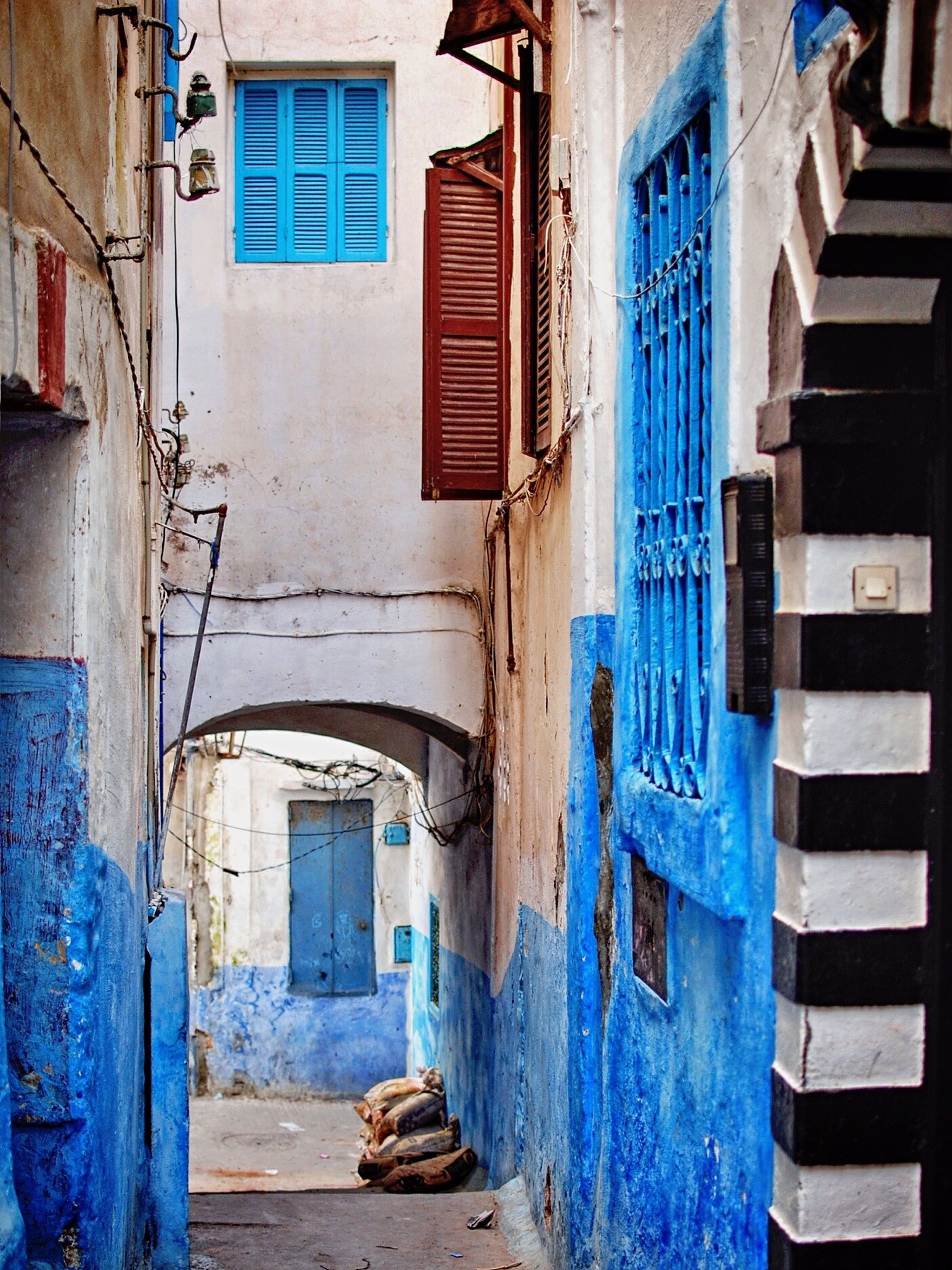 architecture, building exterior, built structure, residential building, residential structure, house, blue, building, window, narrow, wall, street, day, town, wall - building feature, outdoors, no people, city, alley, sunlight