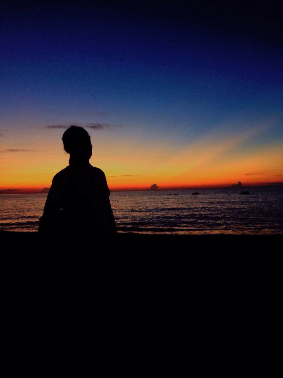 silhouette, sunset, sea, beach, horizon over water, scenics, water, beauty in nature, nature, one person, tranquility, tranquil scene, rear view, sky, real people, outdoors, clear sky, standing, wave, day, people