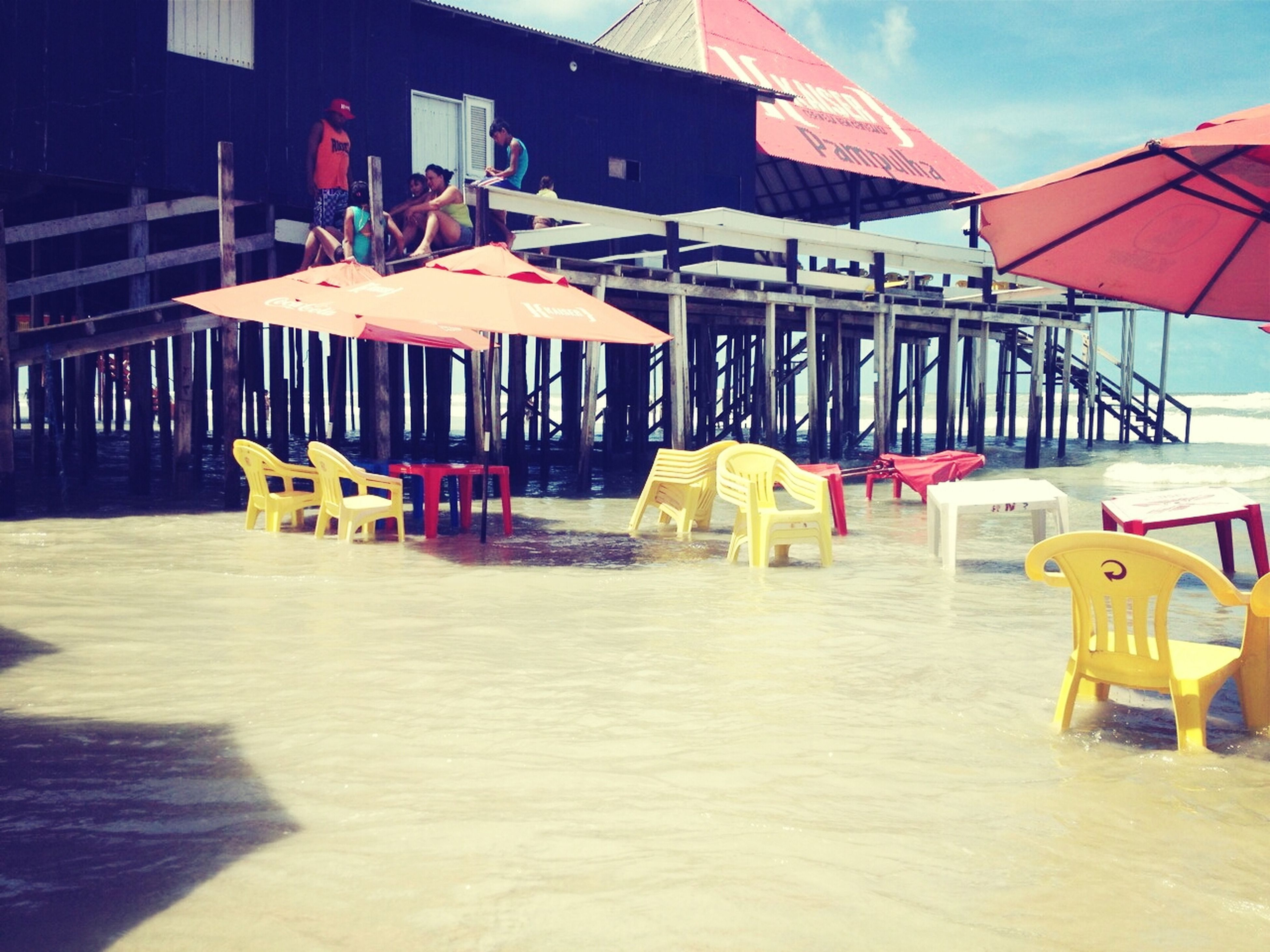 built structure, building exterior, architecture, chair, table, absence, sunlight, sand, beach, parasol, sunshade, flag, lounge chair, sea, group of objects, restaurant, day, outdoors, beach umbrella, in a row